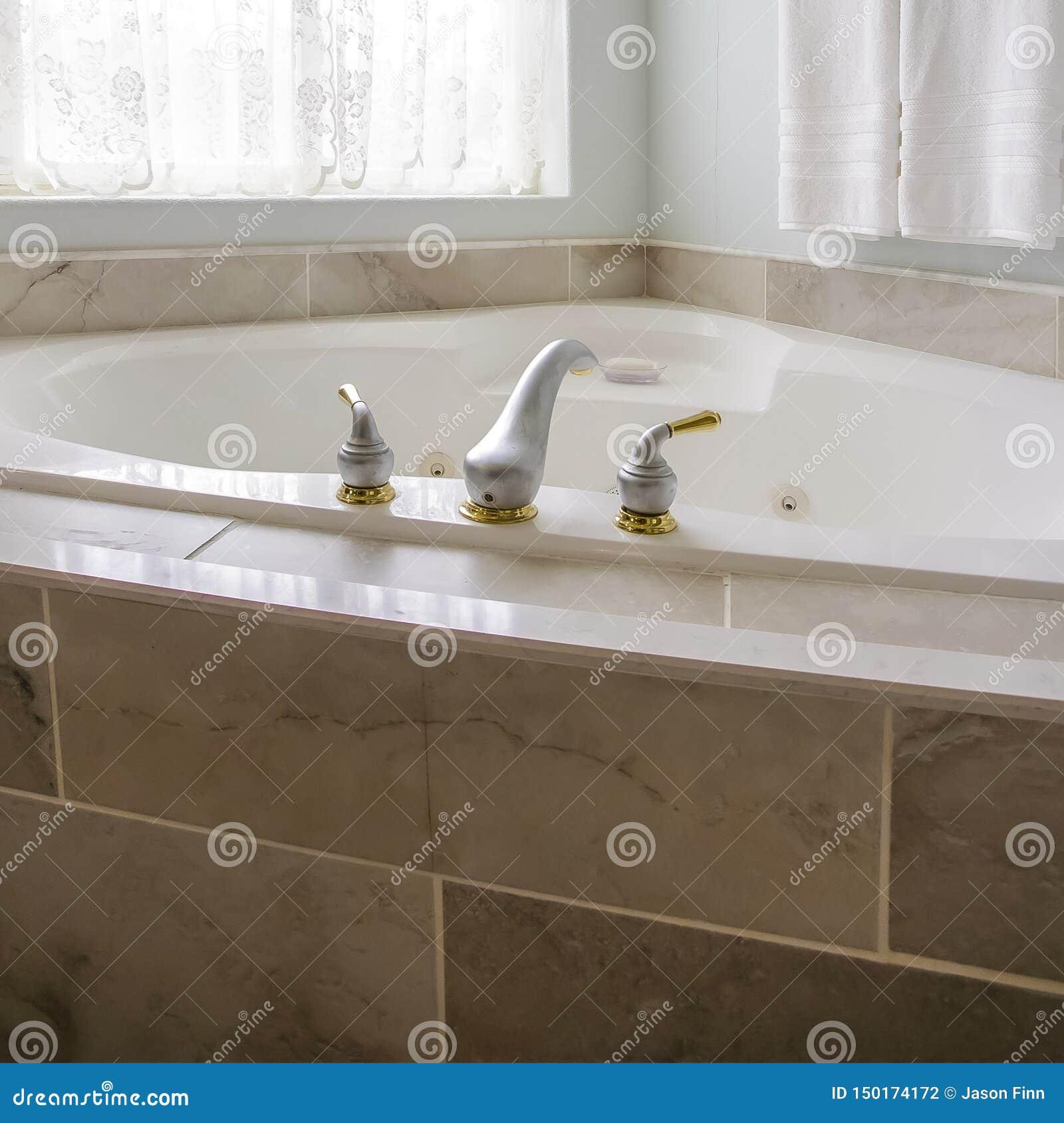 Fyrkant som byggs i badkar på hörnet av ett badrum med ett stort välvt fönster