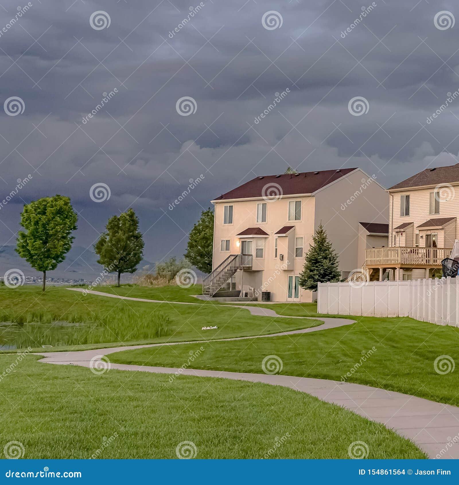 Fyrkantig hem- fasad som förbiser ett expansivt grönt fält med en stenlagt bana och damm