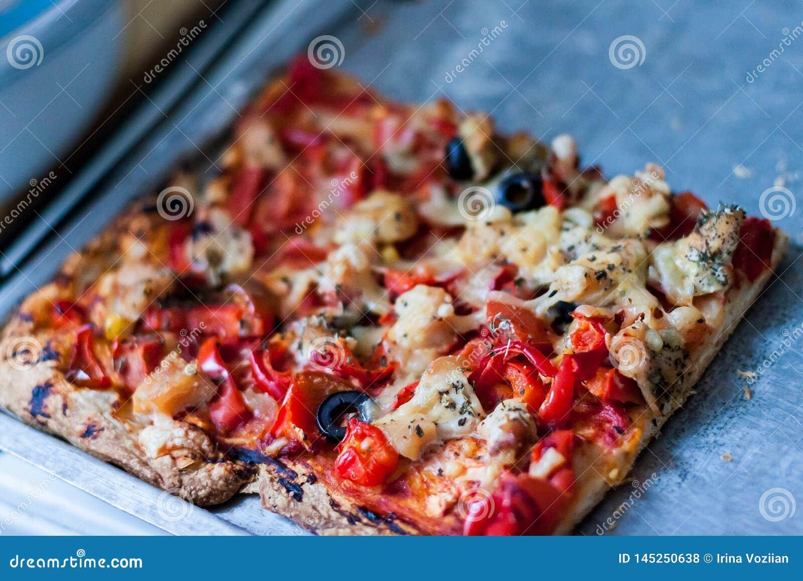 Fyrkantig skiva av pizza på ett grått tennmagasin
