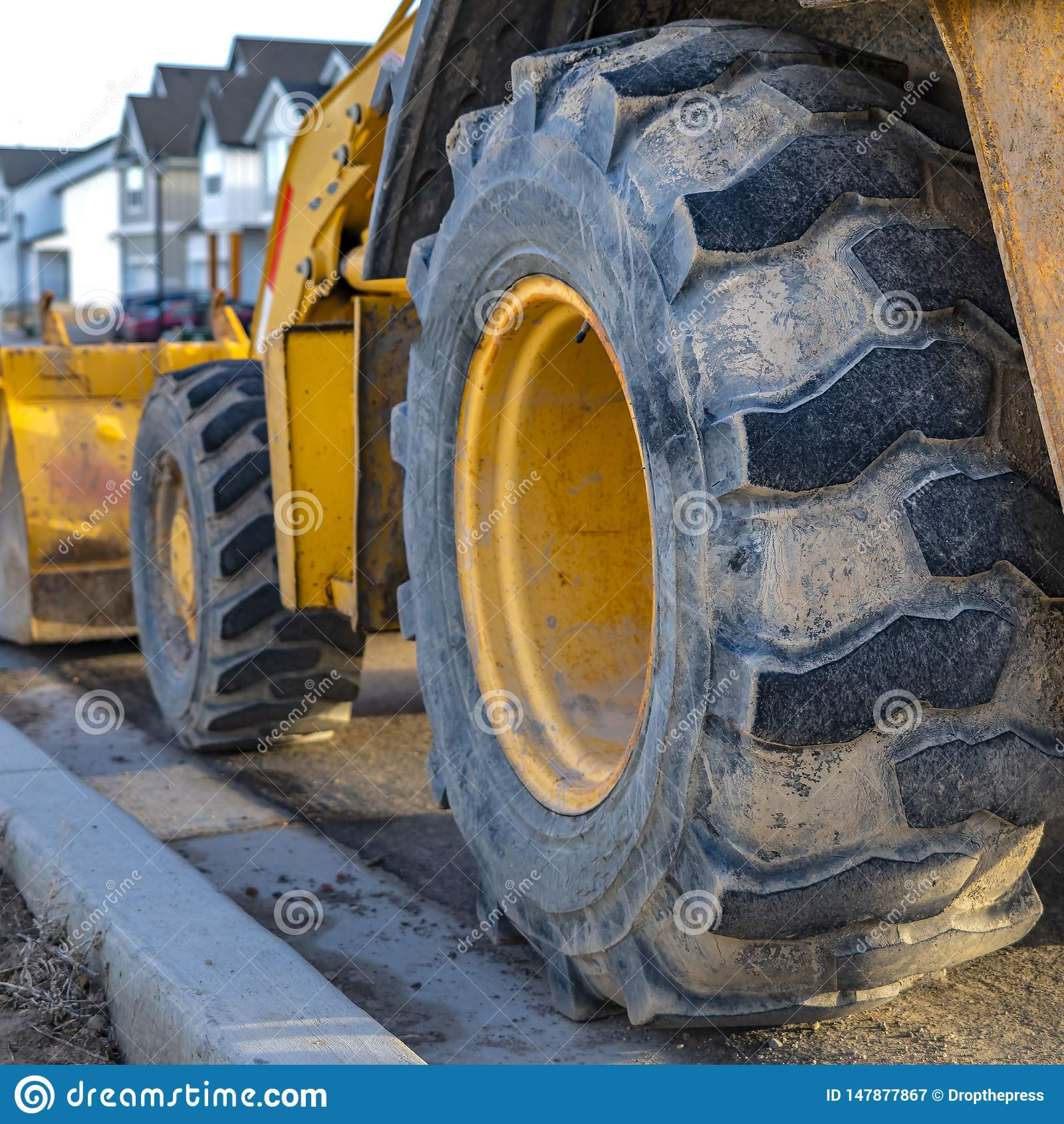 Fyrkantigt slut upp av de smutsiga hjulen av en riden ut laddare som parkeras på en solbelyst väg
