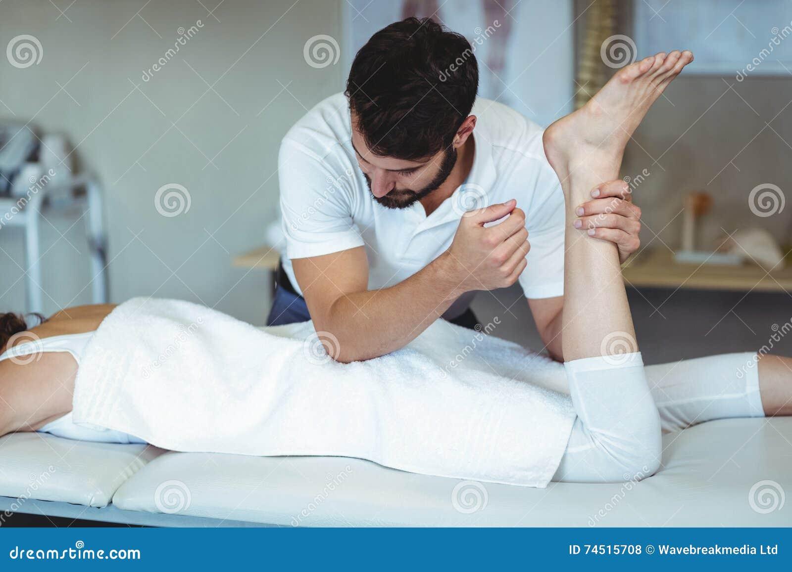 Fysioterapeut som ger höftmassage till en kvinna
