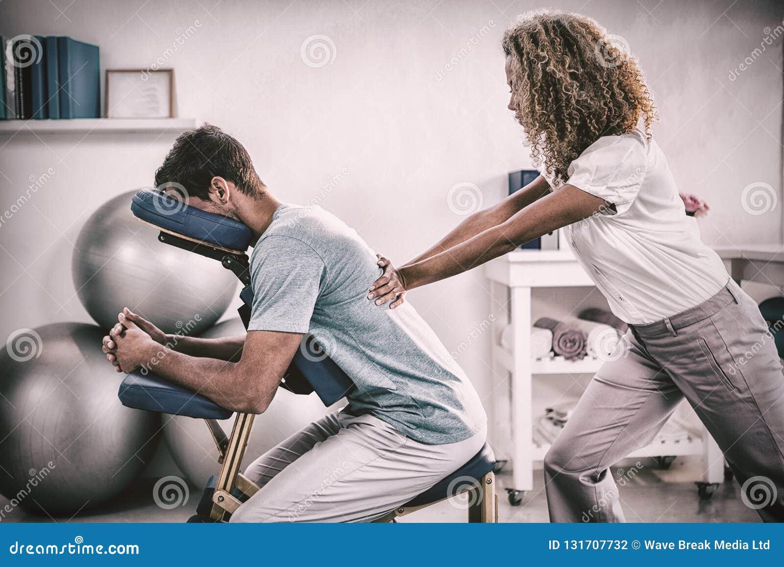Fysioterapeut som tillbaka ger massage till en patient