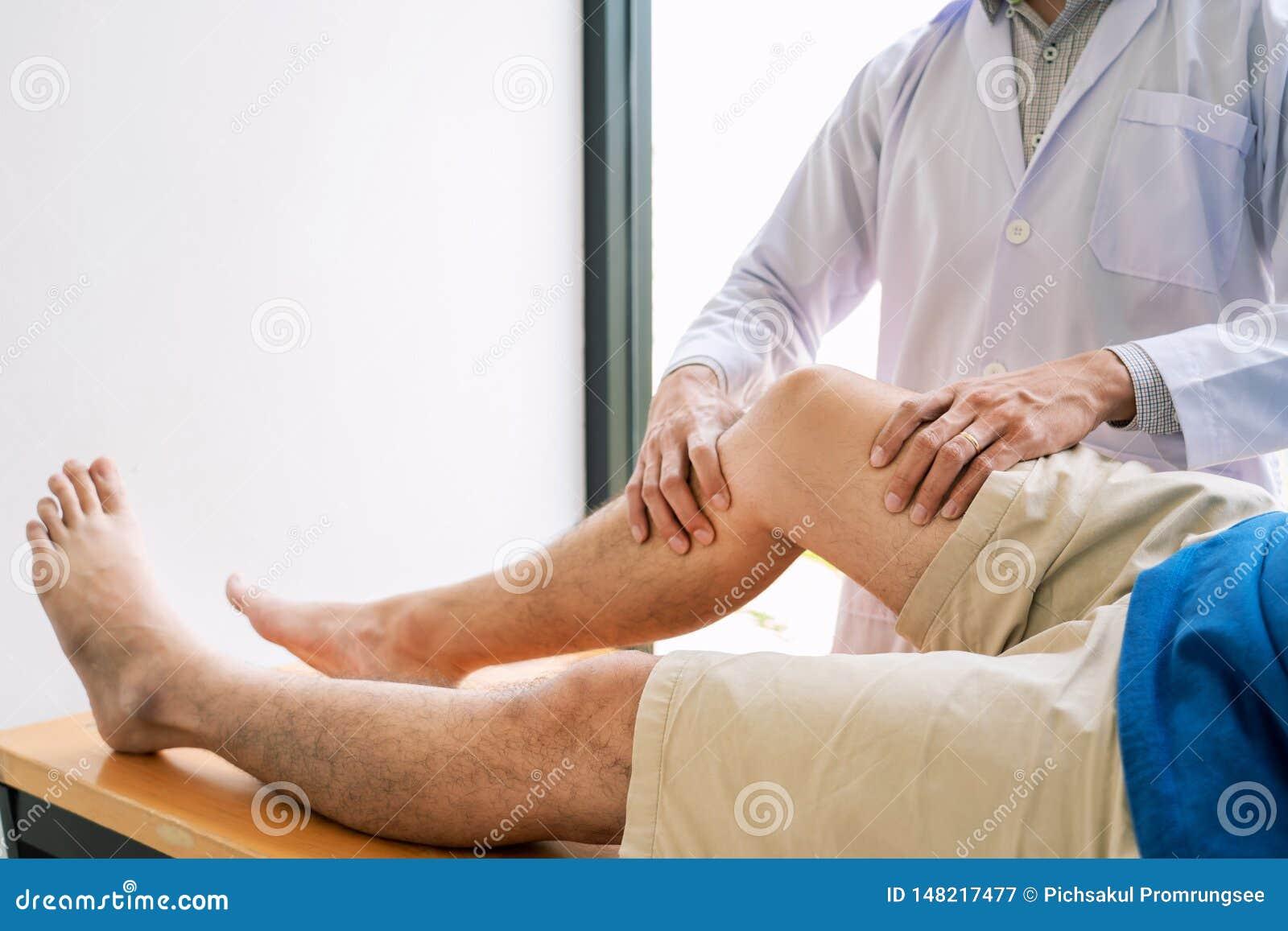 Fysiotherapeut artsenrehabilitatie het raadplegen fysiotherapie die uitoefenend beenbehandeling met pati?nt in fysiokliniek of ho