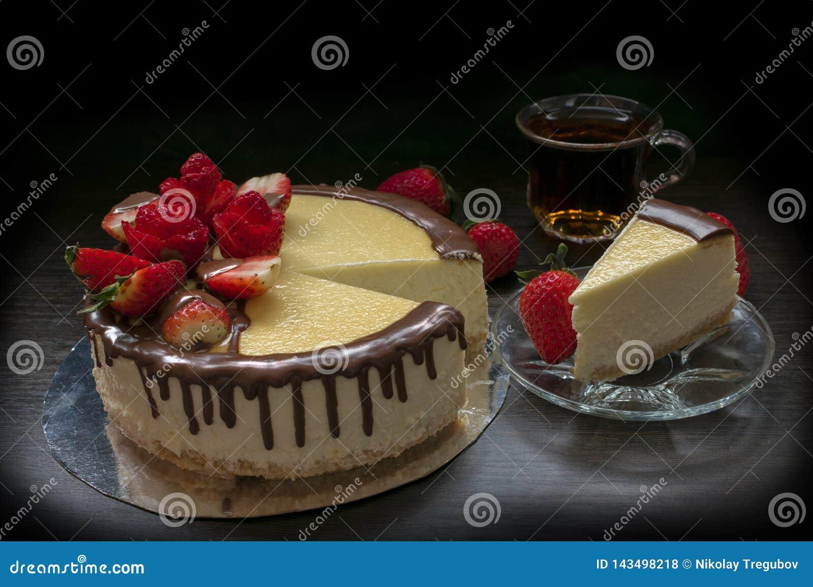 Gâteau au fromage décoré de fraise avec une tasse de thé et de fraises