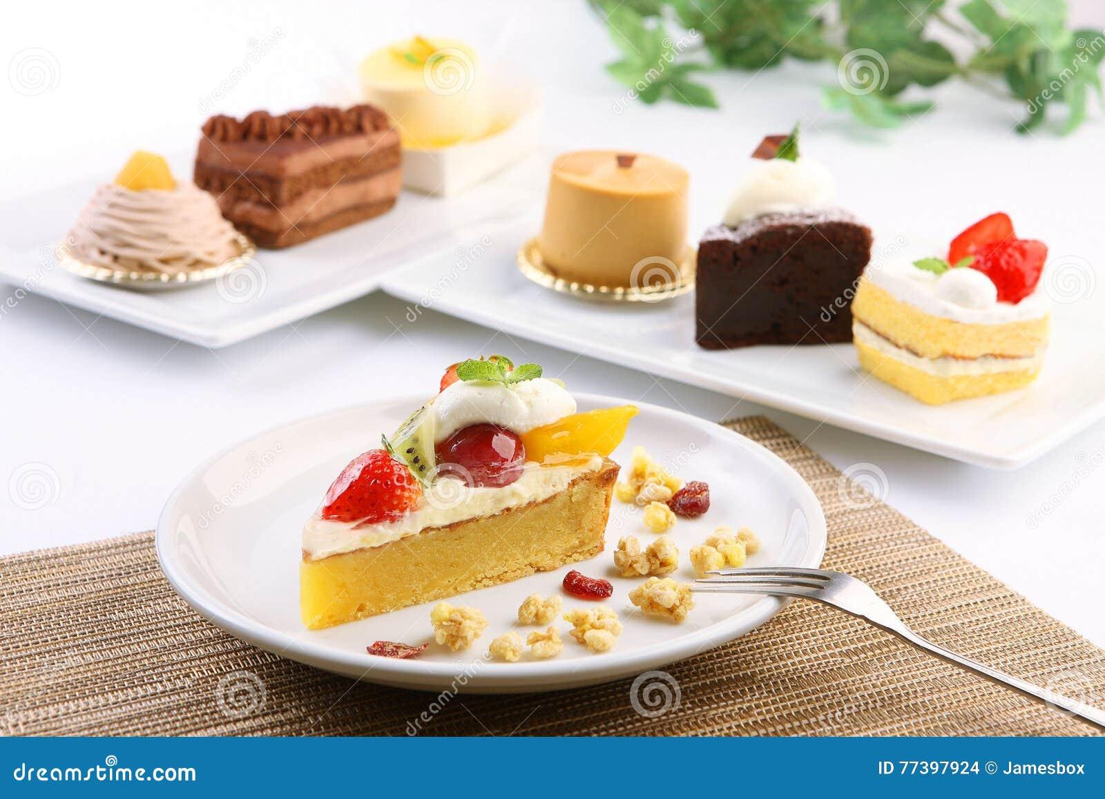 Gâteau crémeux pour le dessert avec la fraise, le kiwi et la mangue sur le blanc