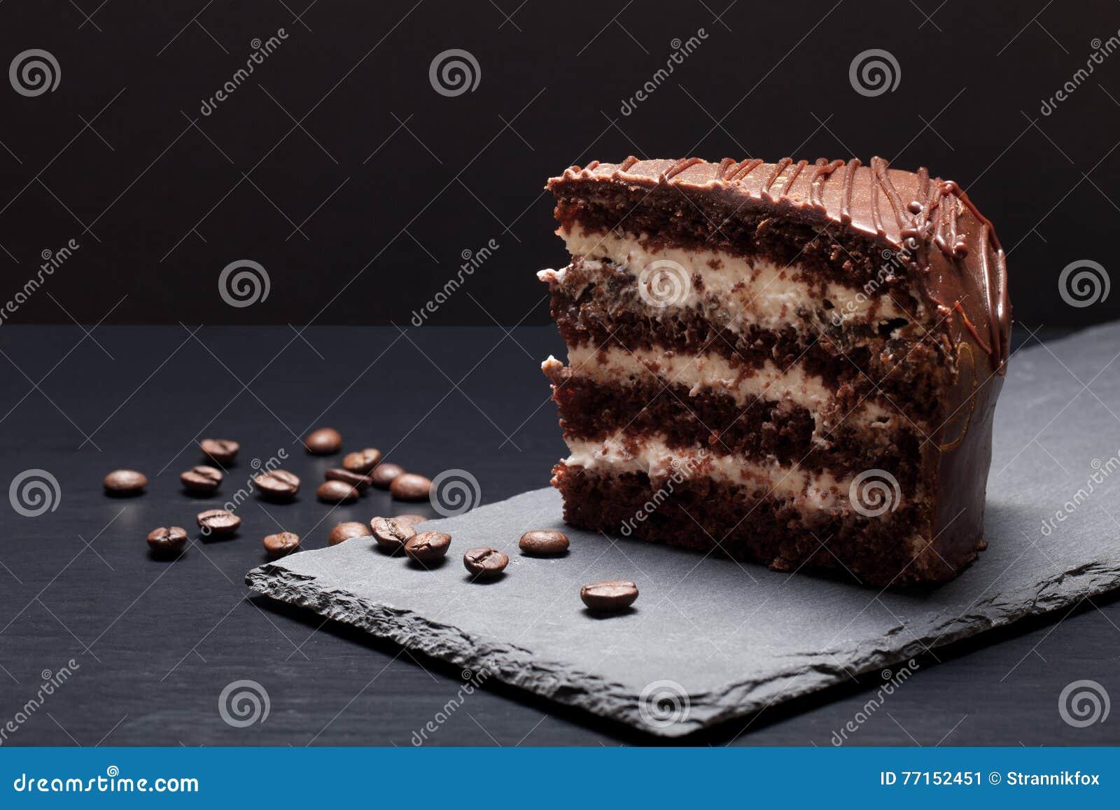 Gâteau de chocolat de plat d ardoise sur le fond noir Foc sélectif