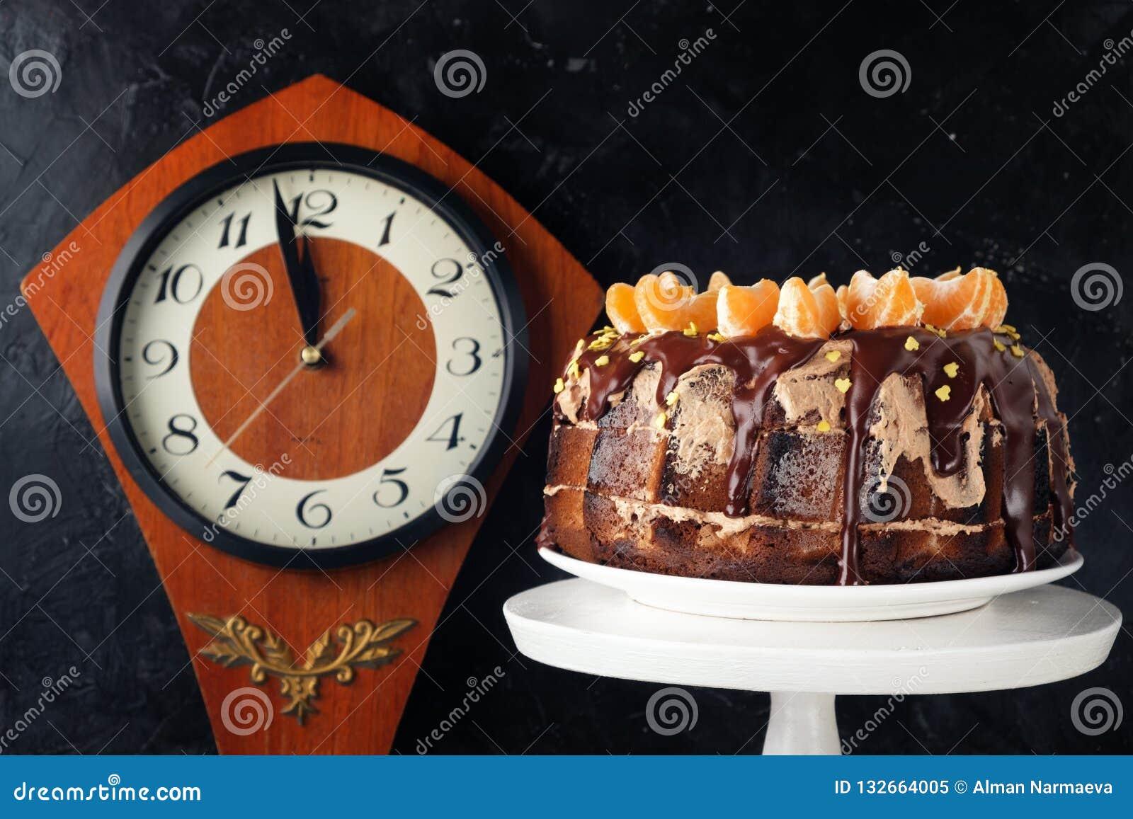 Gâteau de dessert avec le glaçage de chocolat décoré des mandarines sur un fond noir Horloge en bois