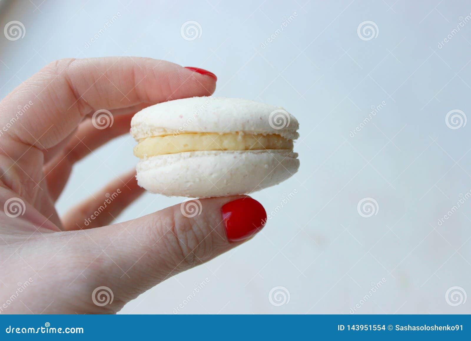 Gâteau de macaronis dans la main de la fille sur un fond clair, en gros plan