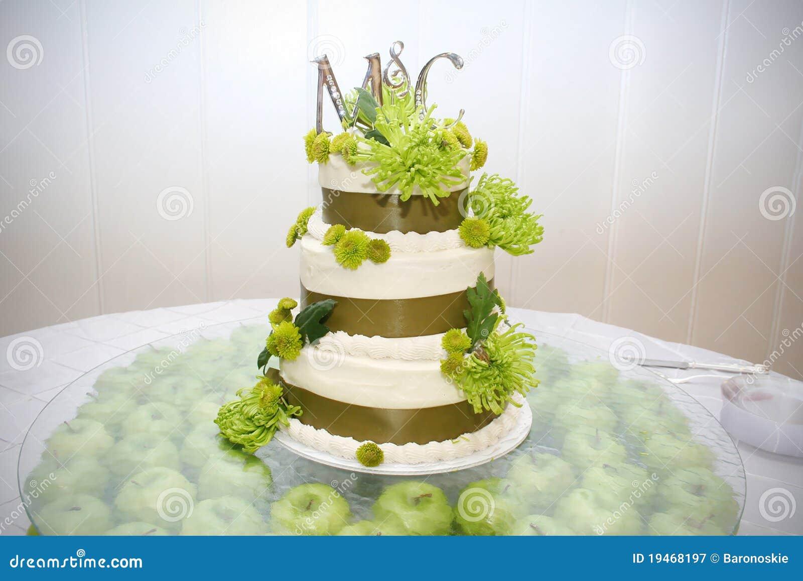 Un gâteau de mariage est décoré de vert et de brun et se repose sur ...