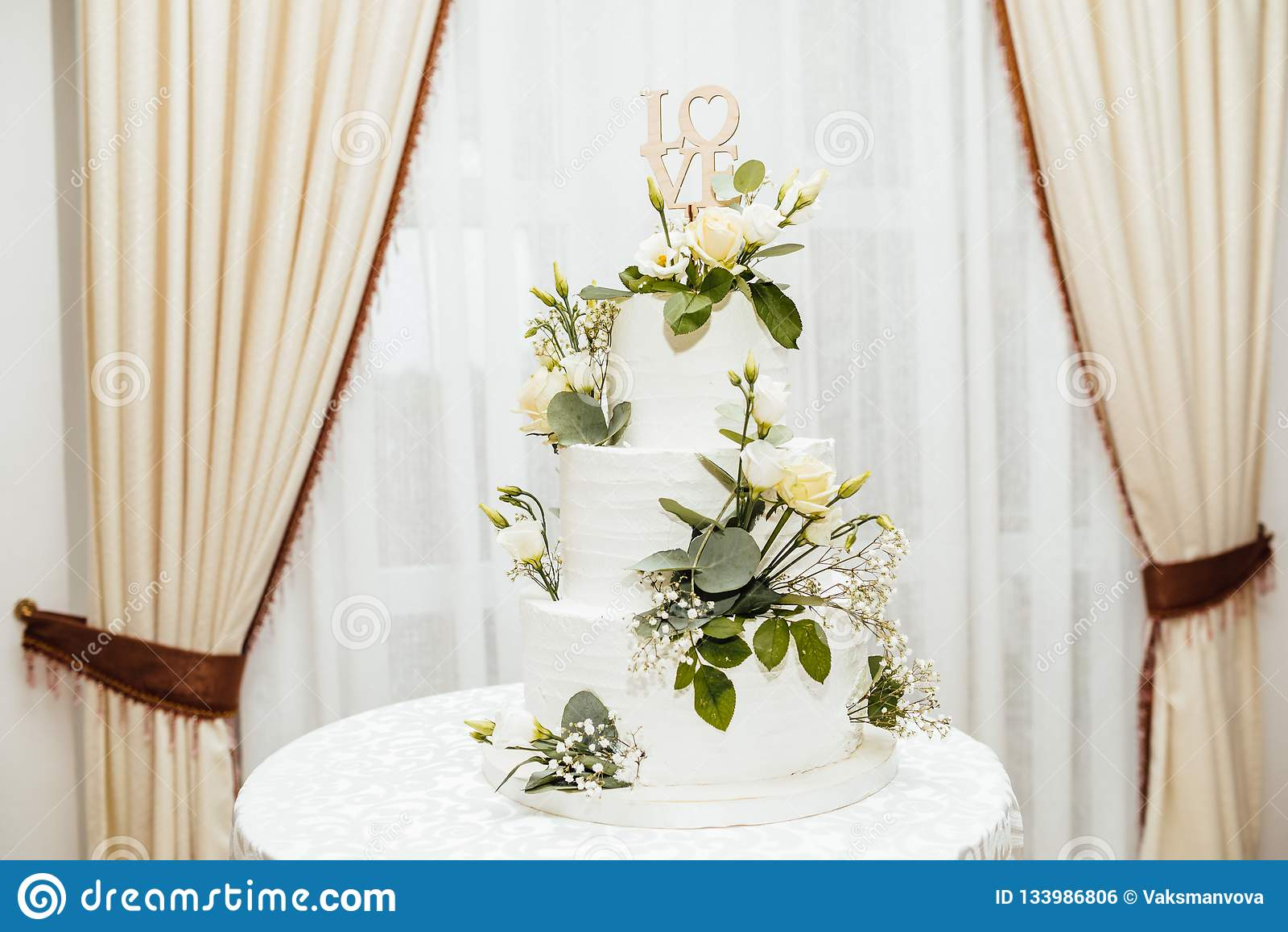 Gâteau de mariage blanc avec des fleurs L amour de mot avec le coeur