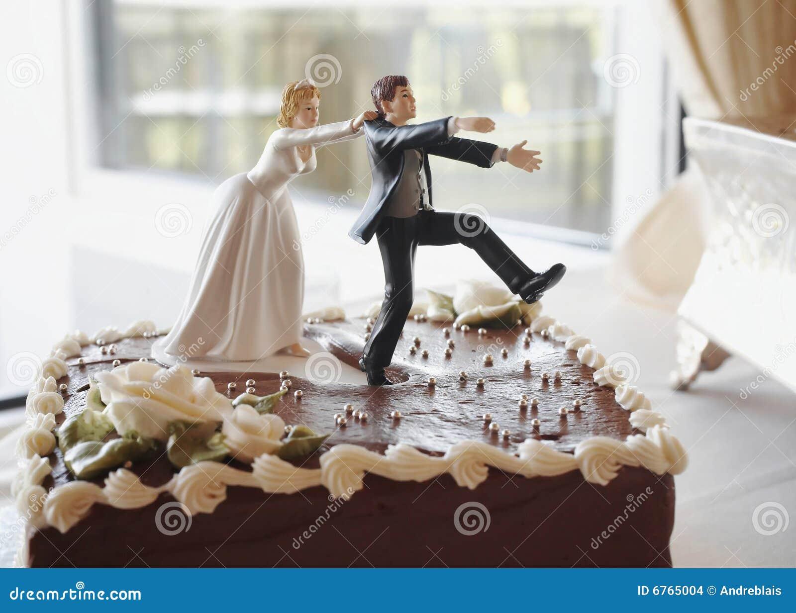 Mariée drôle de dessus de gâteau de mariage chassant le marié.