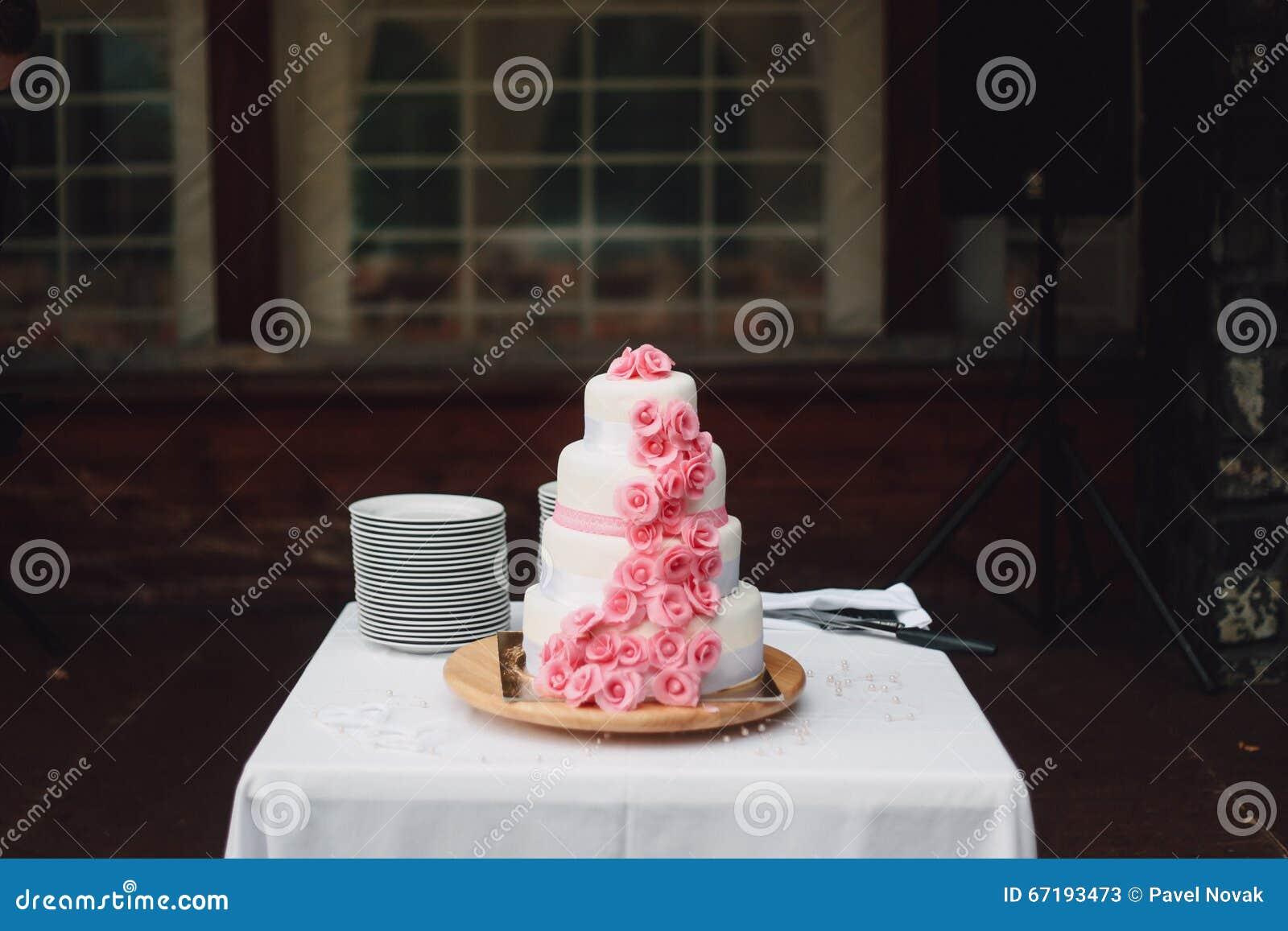 Gâteau de mariage rose blanc avec des roses sur le bureau