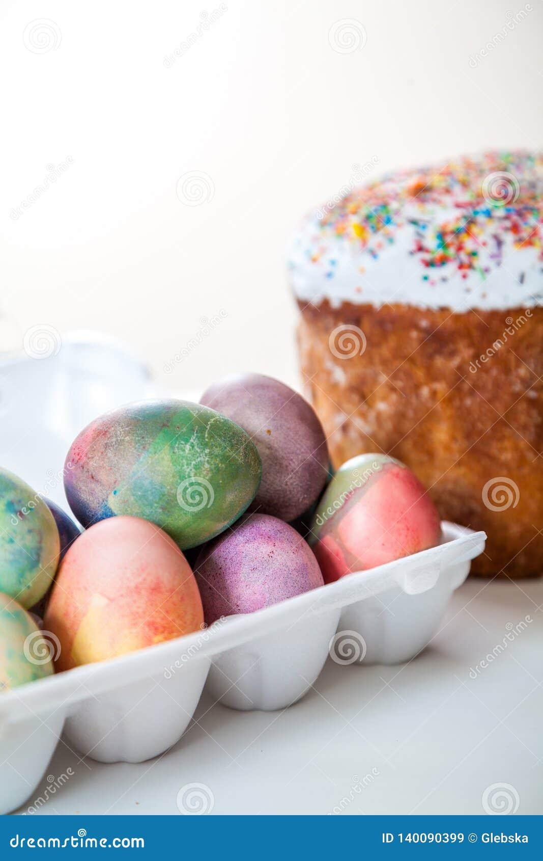 Gâteau de Pâques et oeufs colorés dans le plateau sur le fond blanc