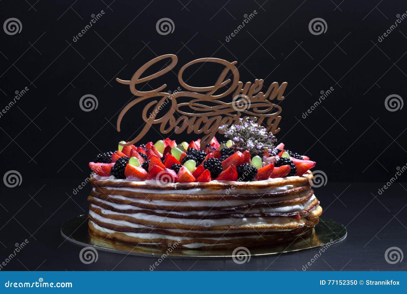 Gâteau fait maison de biscuit avec de la crème et des baies sur le fond noir