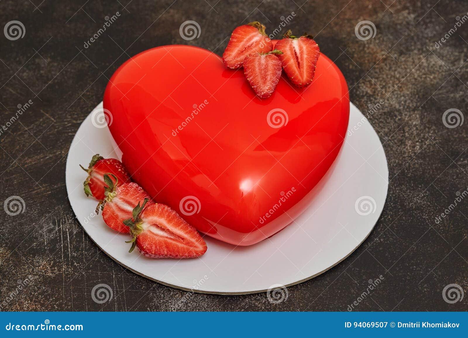 Gâteau rouge de mousse de lustre, forme de forme de coeur sur le fond foncé
