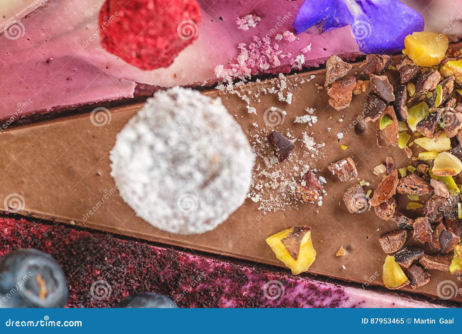 Gâteaux crus de vegan avec le fruit et les graines, décorés de la fleur, photographie de produit pour la pâtisserie