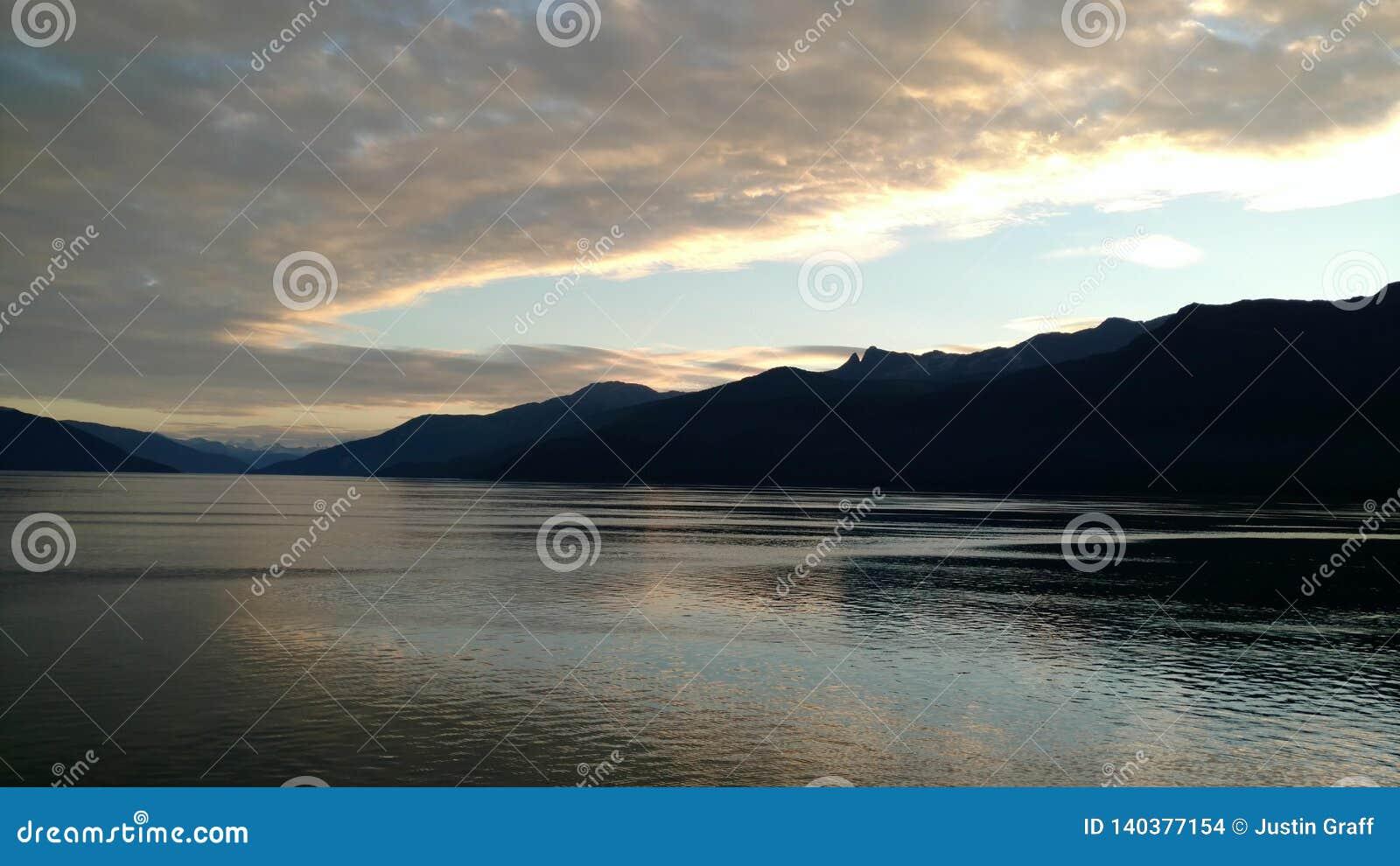 Góra Wypełniający horyzont na oceanie spokojnym Wśrodku przejścia Alaska przy zmierzchem