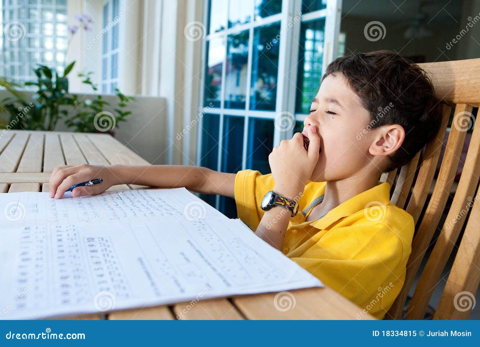 Gähnender Junge beim Handeln seiner Heimarbeit
