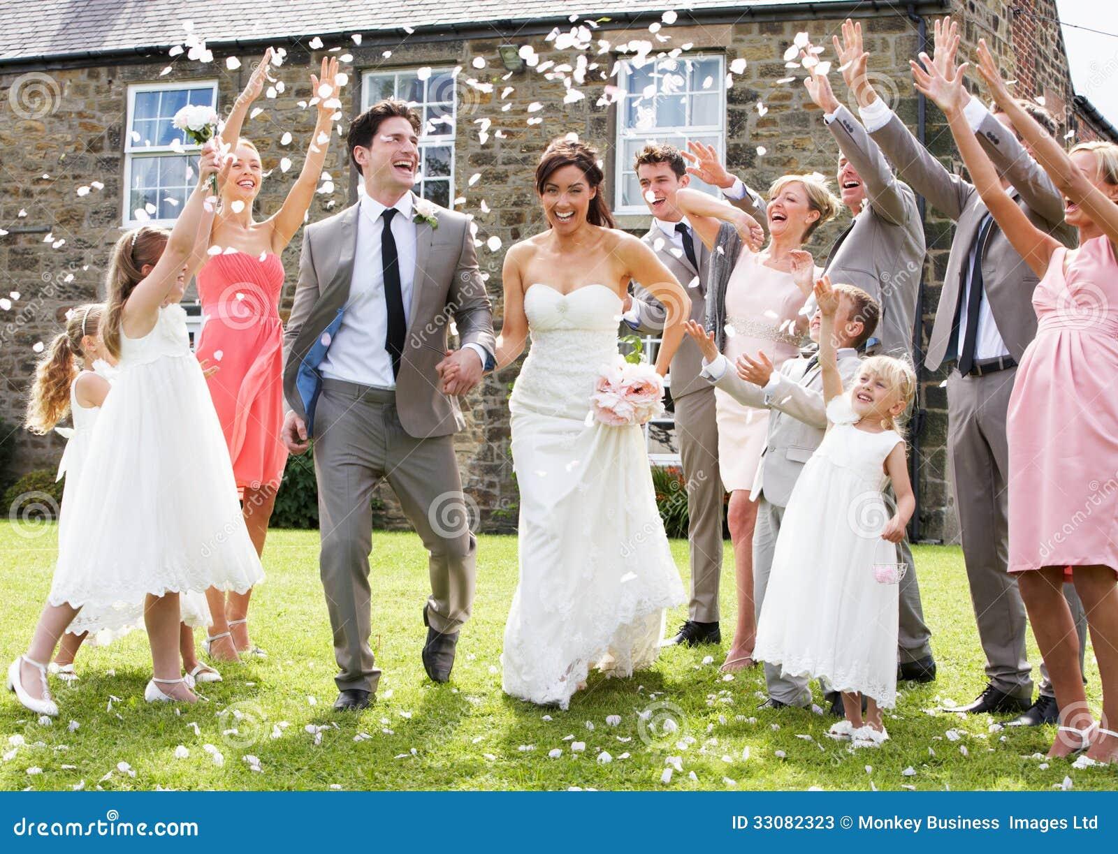 Gäste, die Konfettis über Braut und Bräutigam werfen