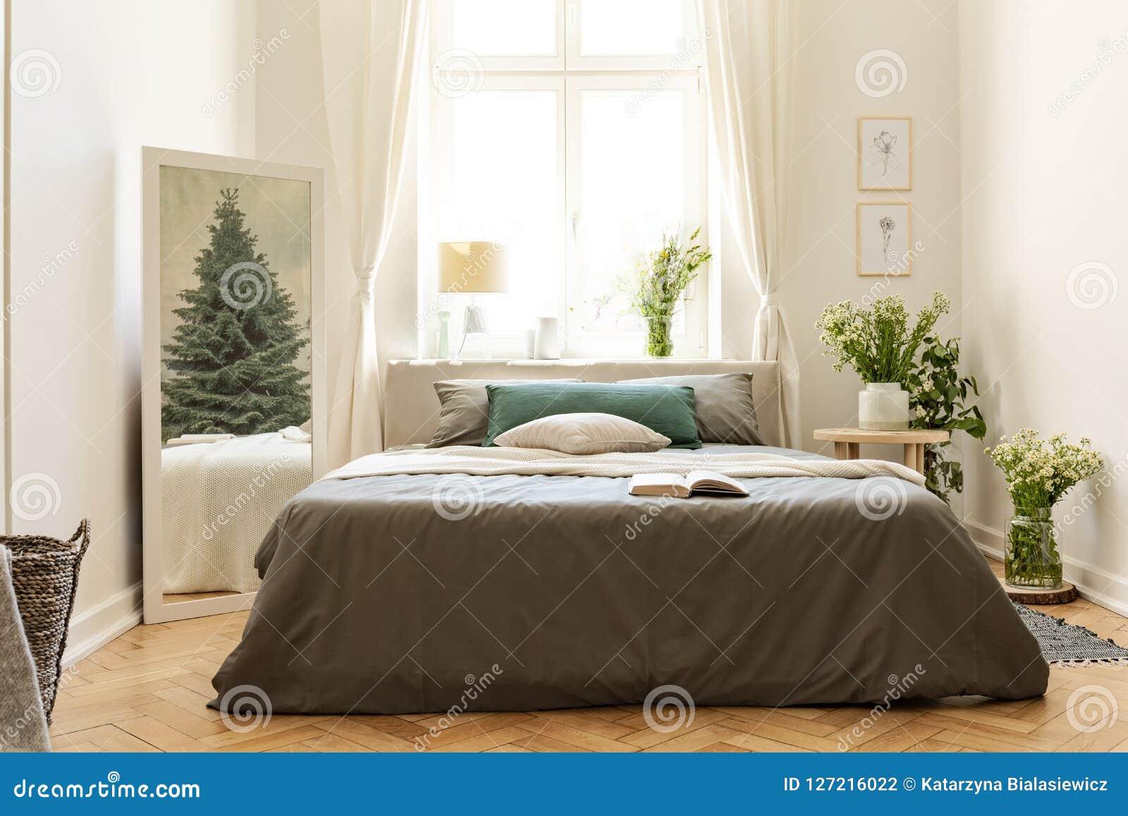 Gästhemsovruminre med en säng, grupper av lösa blommor och en vintergrön trädreflexion i spegeln Verkligt foto