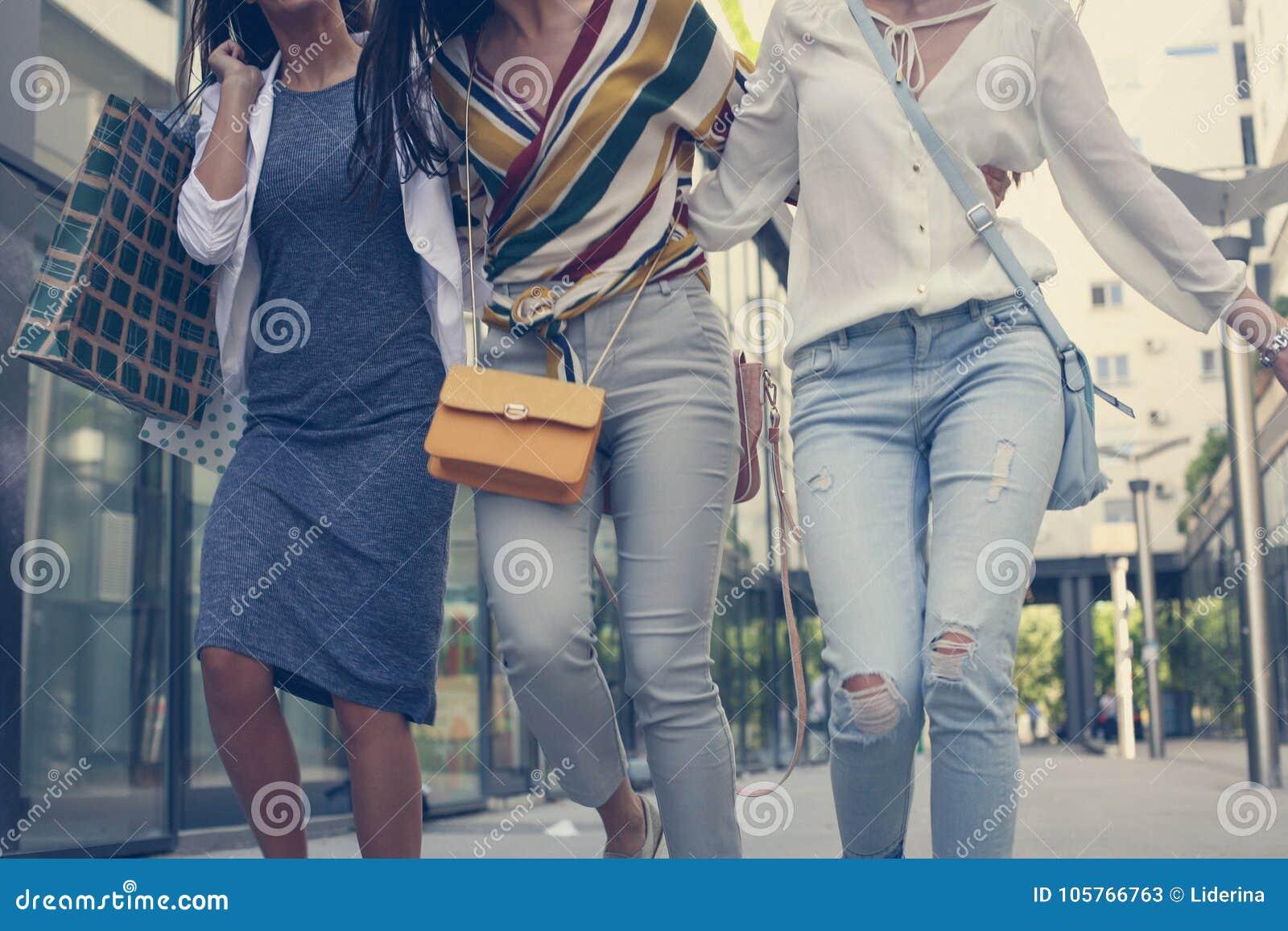Gå för tre unga flickor som är lyckligt med shoppingpåsar
