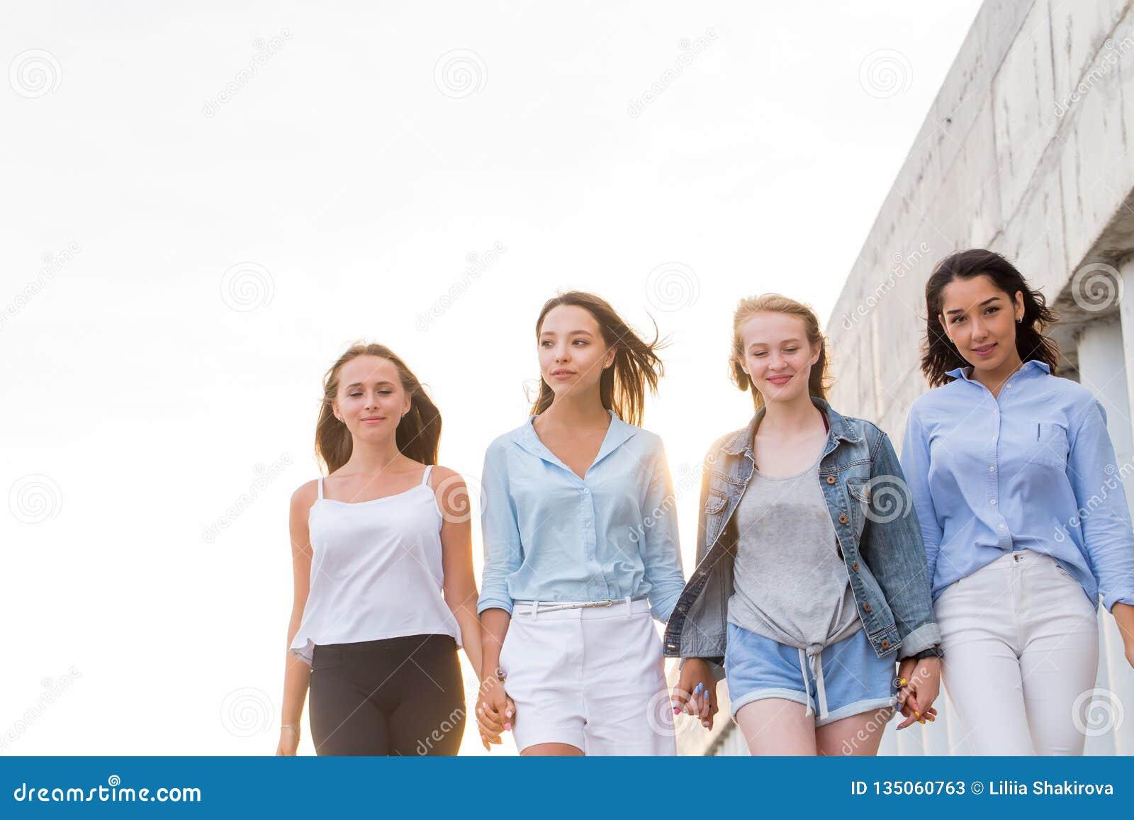 Gå fyra lyckliga vänner på gatan i bakgrunden av en vit himmel med kopieringsutrymme