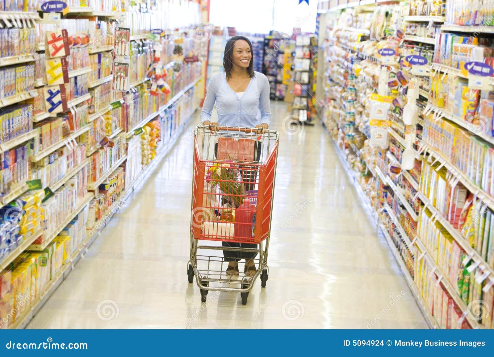 Gång längs att skjuta supermarkettrolleykvinnan
