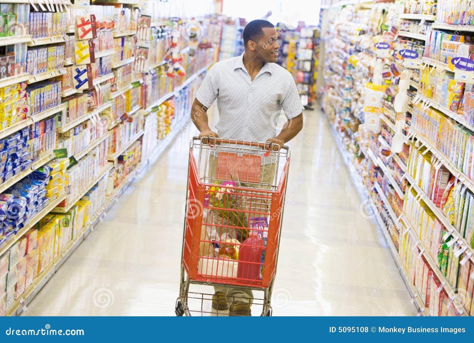 Gång längs mannen som skjuter supermarkettrolleyen