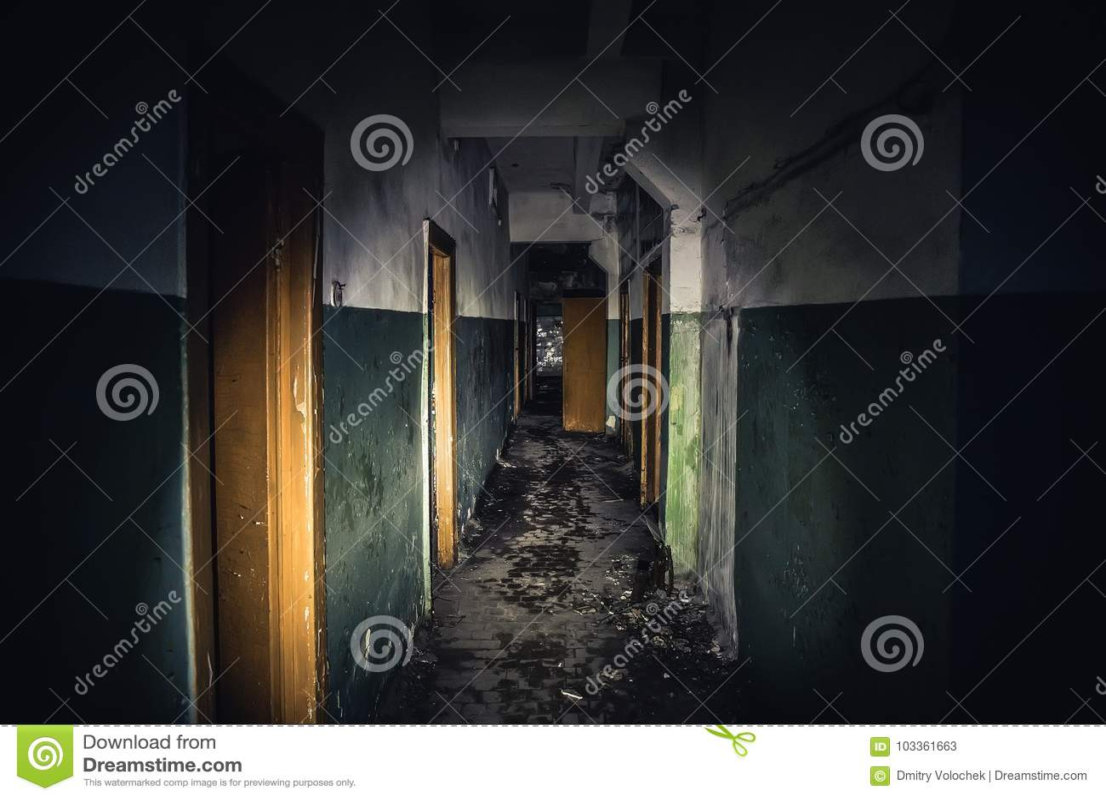 Gångbana i kuslig övergiven byggnad, mörk läskig korridor med många dörrar, fasabakgrundsbegrepp