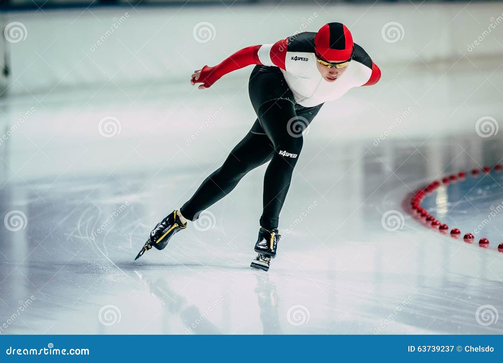 Går speedskateren för idrottsman nen för den unga kvinnan för closeupen runt om vänd av isbanan