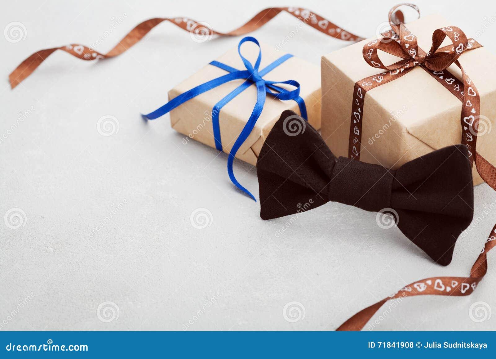 Gåva eller gåvaask med bandet och bowtie på det gråa skrivbordet för lycklig faderdag, kopieringsutrymme för din text eller desig