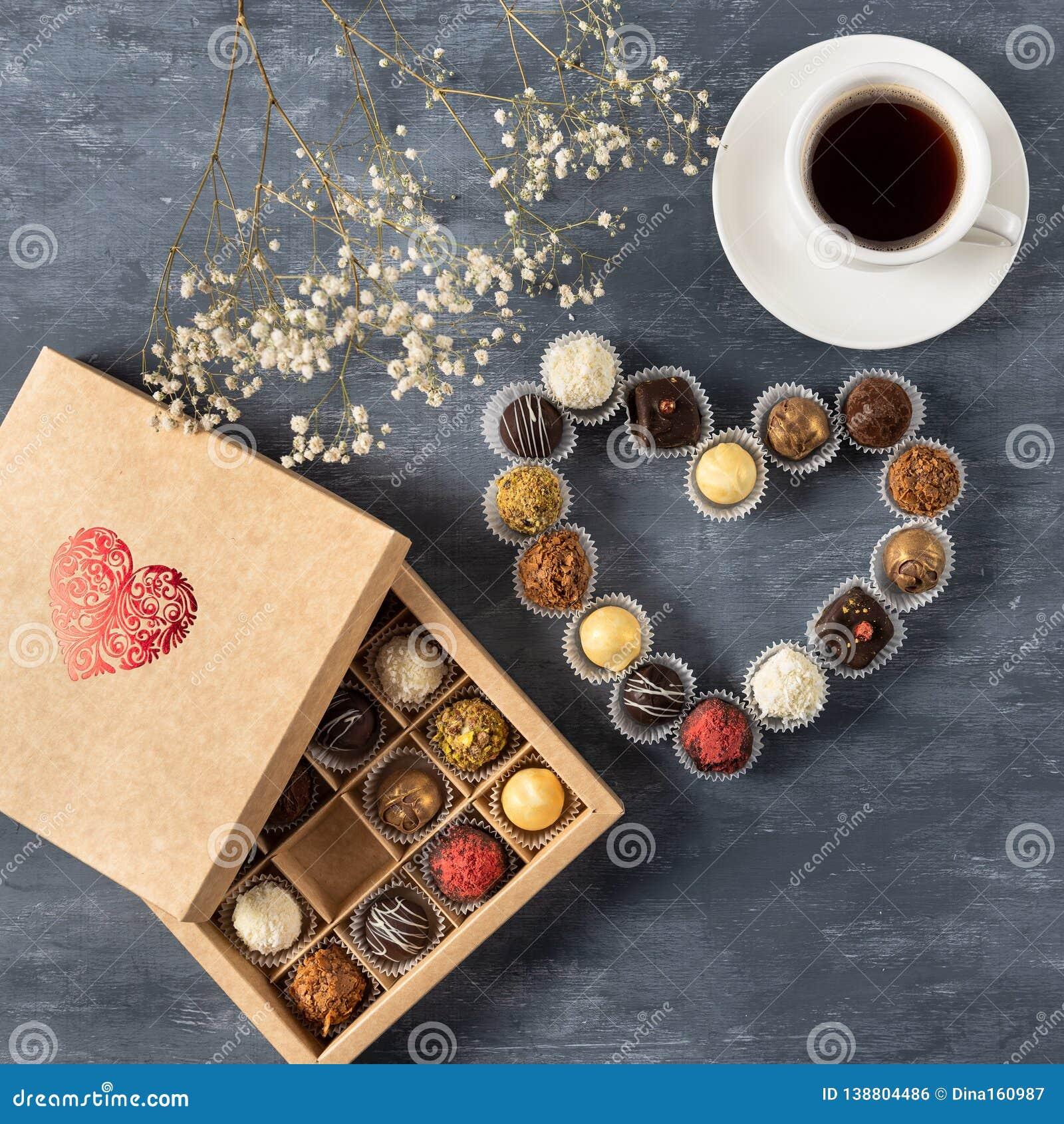 Gåvaask av gourmet- choklader för valentin dag på mörk bakgrund med koppen kaffe, bästa sikt, kopieringsutrymme