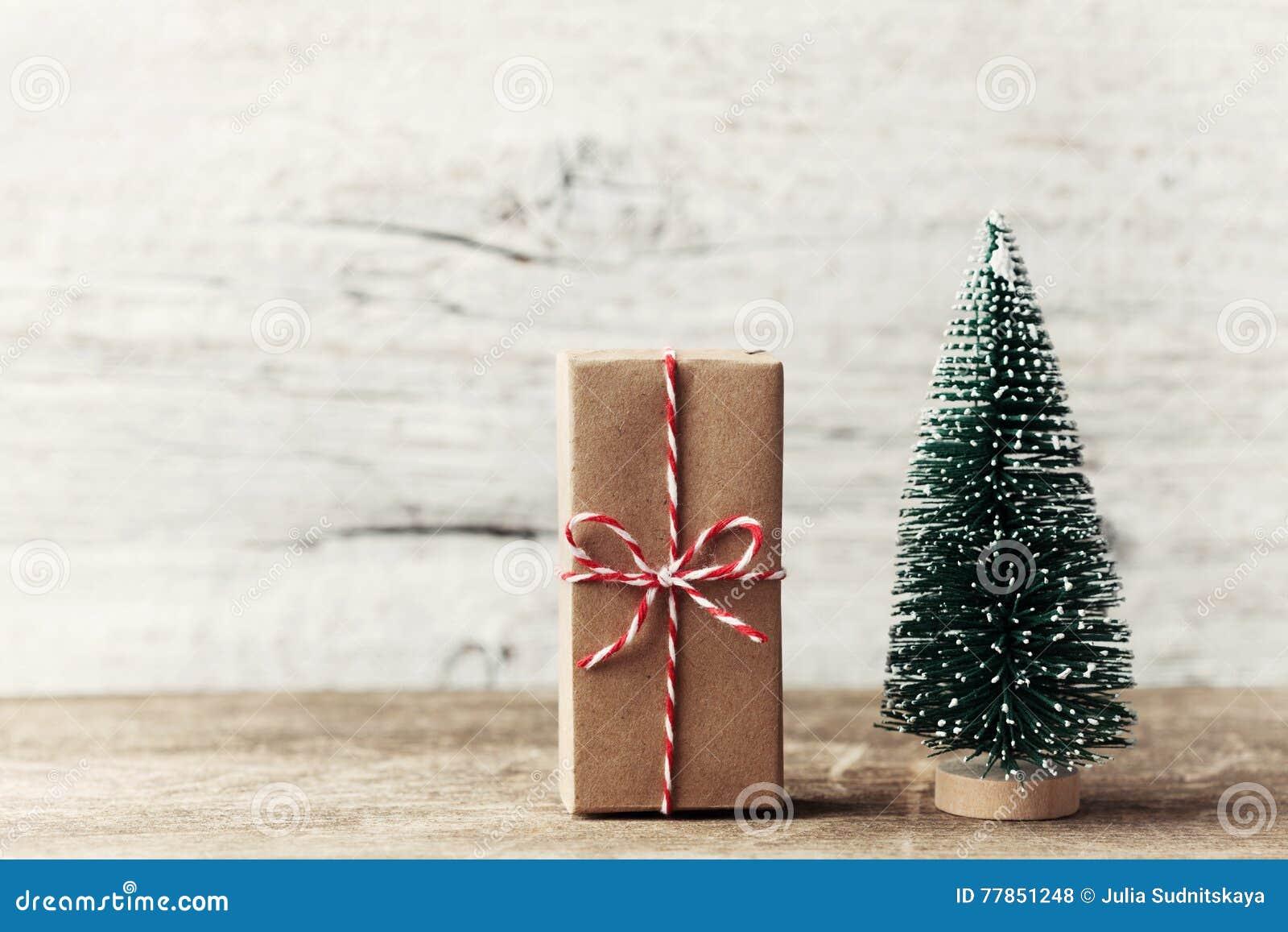 Gåvaask som slås in i kraft papper och litet dekorativt granträd på trälantlig bakgrund nytt år för julbegrepp