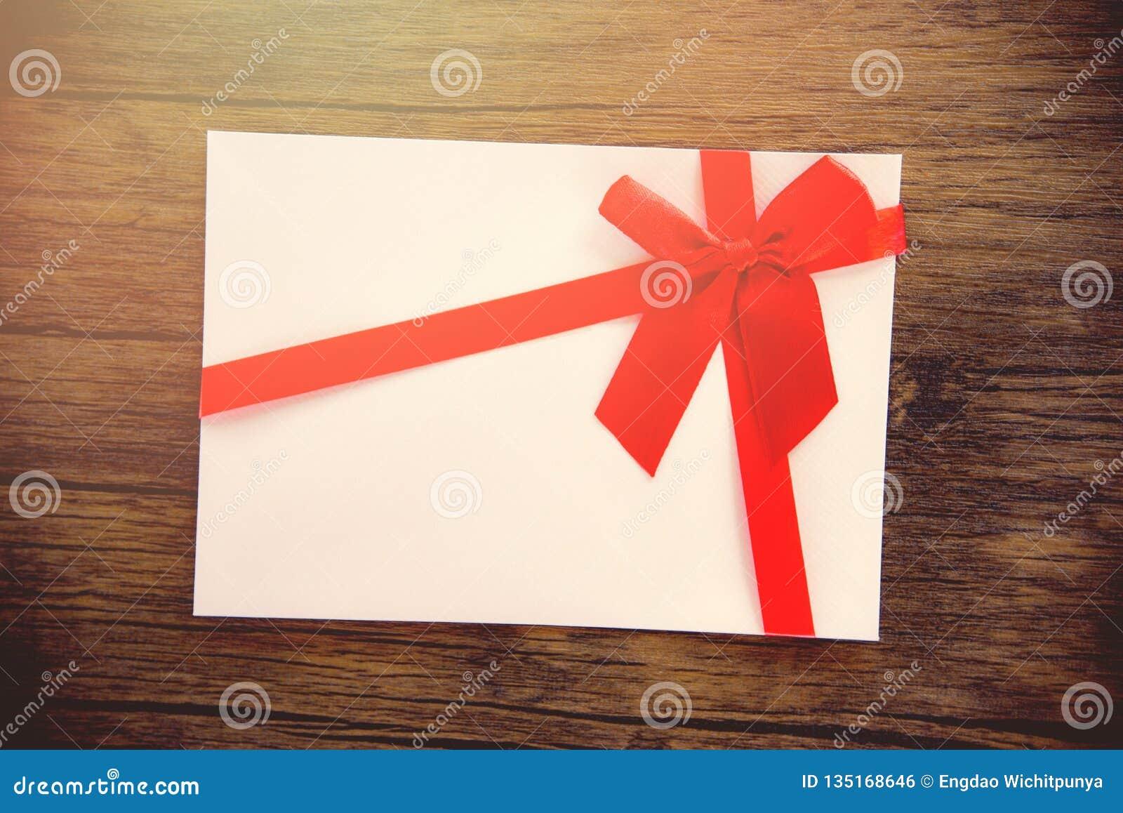 Gåvakort på det rosa vita gåvakortet för träbakgrund som dekoreras med den röda bandpilbågen till året för ferie för glad jul det
