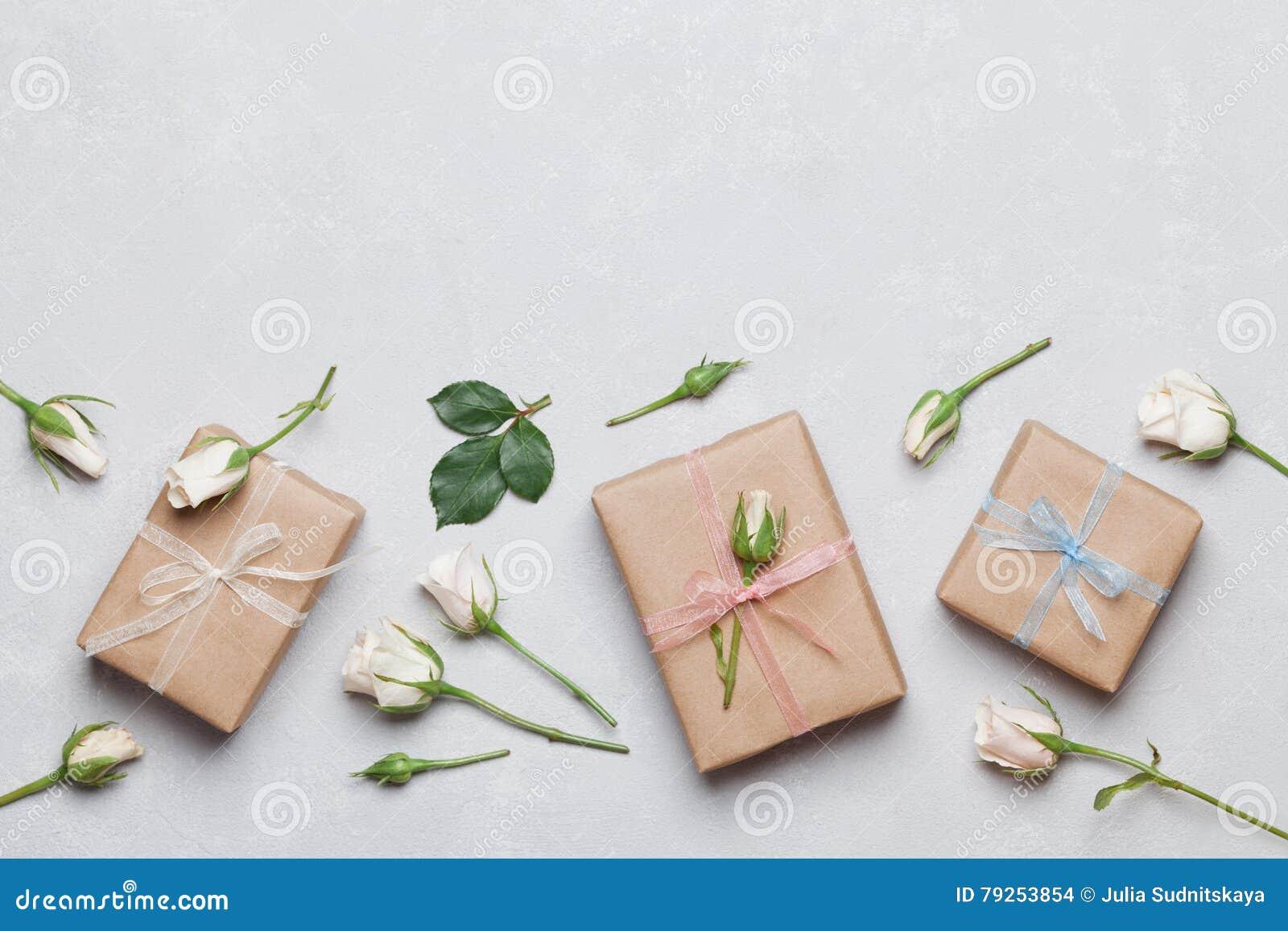 Gåvan eller gåvaasken som slås in i den kraft papper och rosen, blommar på grå bästa sikt för tabell Lekmanna- utforma för lägenh