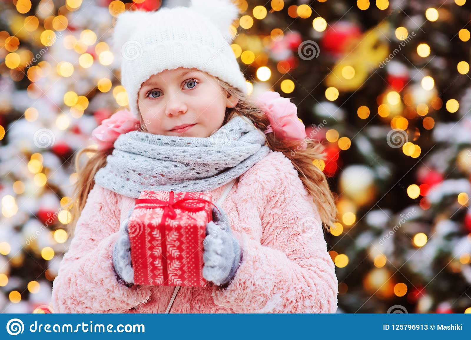 Gåvan för jul för den lyckliga barnflickan som semestrar den hållande är utomhus- på gå i den snöig vinterstaden som dekoreras fö