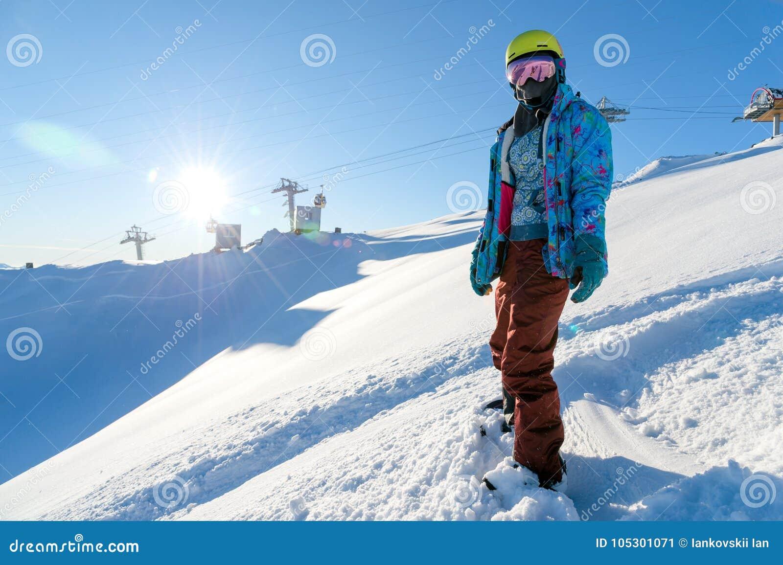 GÓRA ELBRUS ROSJA, LISTOPAD, - 30, 2017: Snowboard dziewczyna jest ubranym słońce maskę i szalika jest statywowa na skłonie _