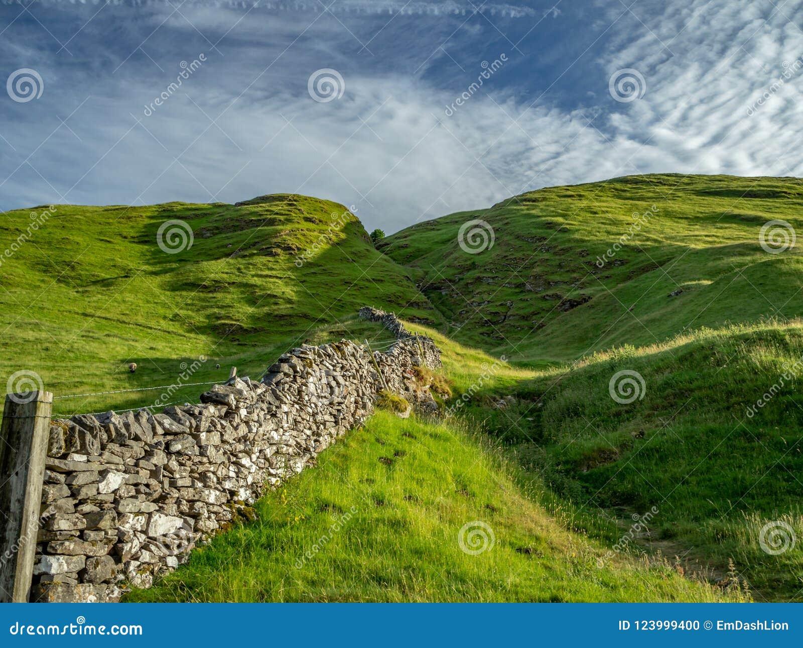 Górkowaty krajobraz w Szczytowym okręgu w UK z kamiennym fenc
