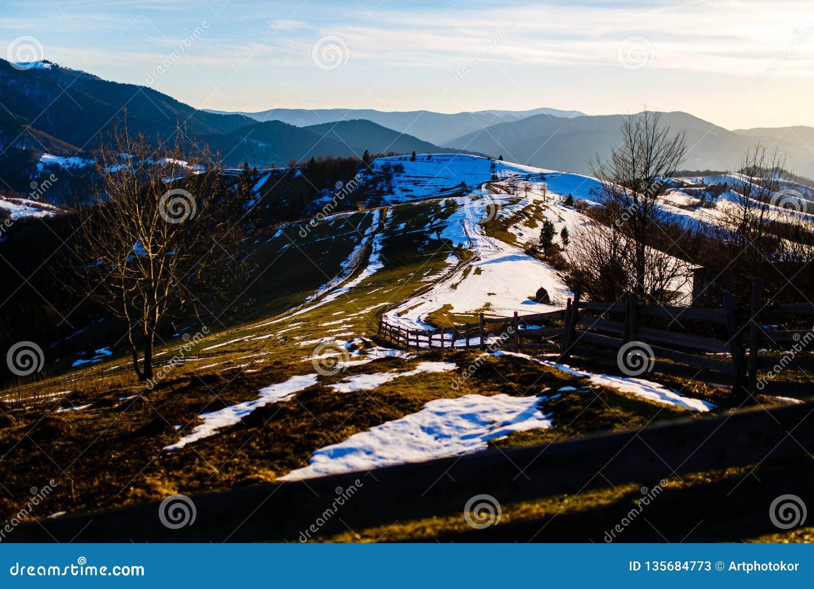 Górkowaty teren zakrywający z roztapiającym śniegiem niebieska spowodowana pola pełne się chmura dzień zielonych roślin krajobraz