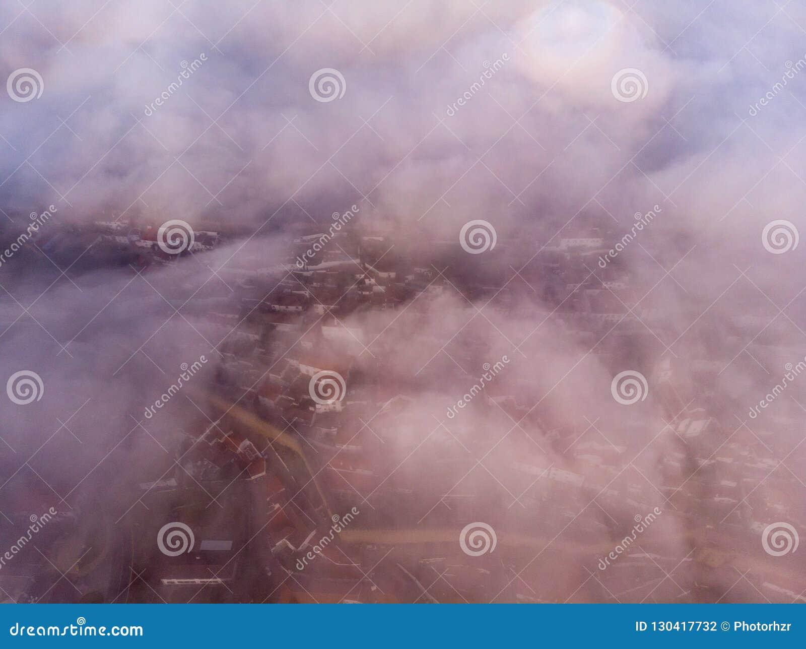 Górny widok czerwoni dachy mały miasto blisko rzeki wśród wzgórzy przeciw niebieskiemu niebu i bielowi chmurnieje