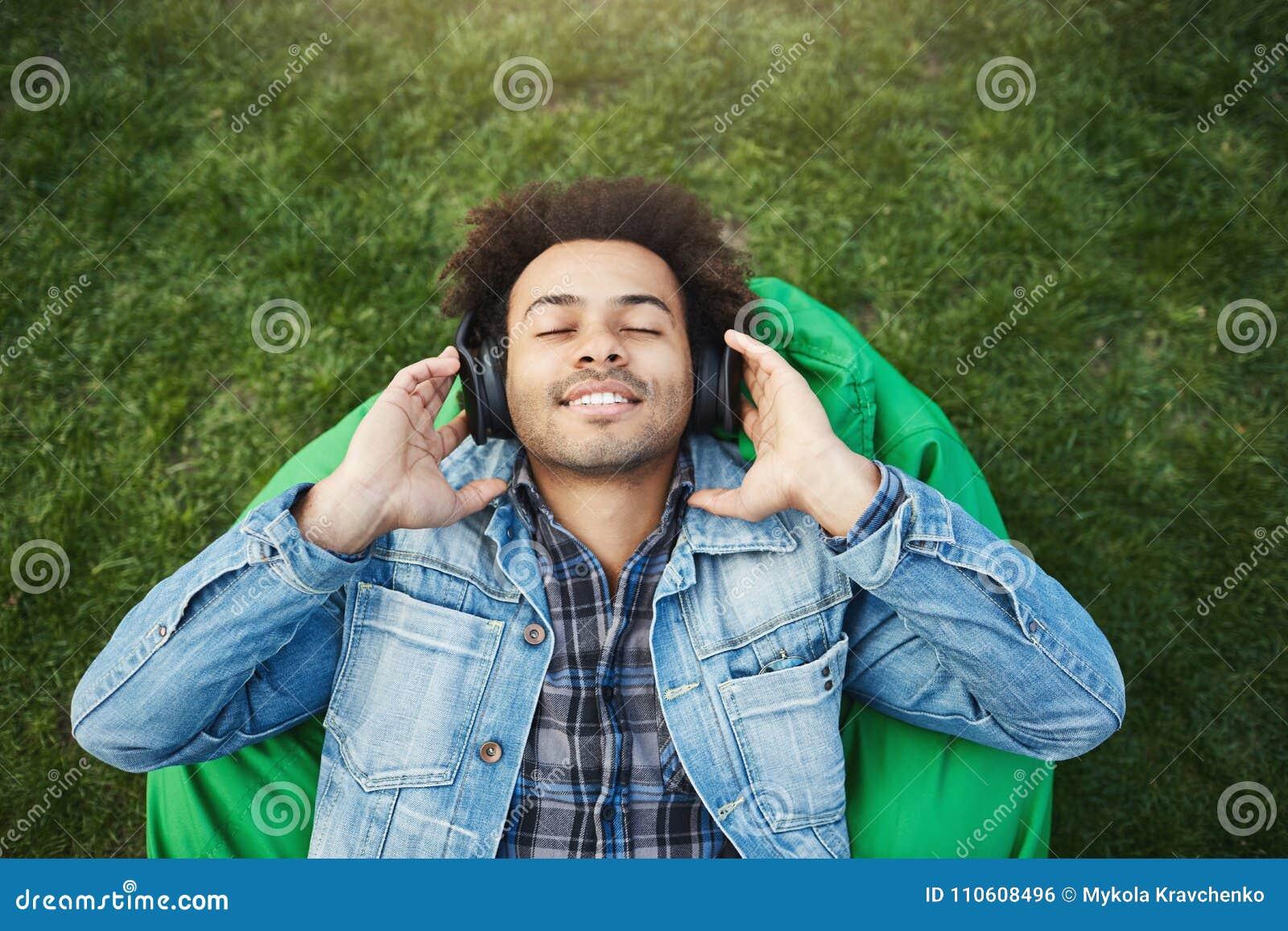 Górny widoku portret zadowolony zrelaksowany afroamerykański mężczyzna kłama na trawie z szczecina podczas gdy słuchający muzykę