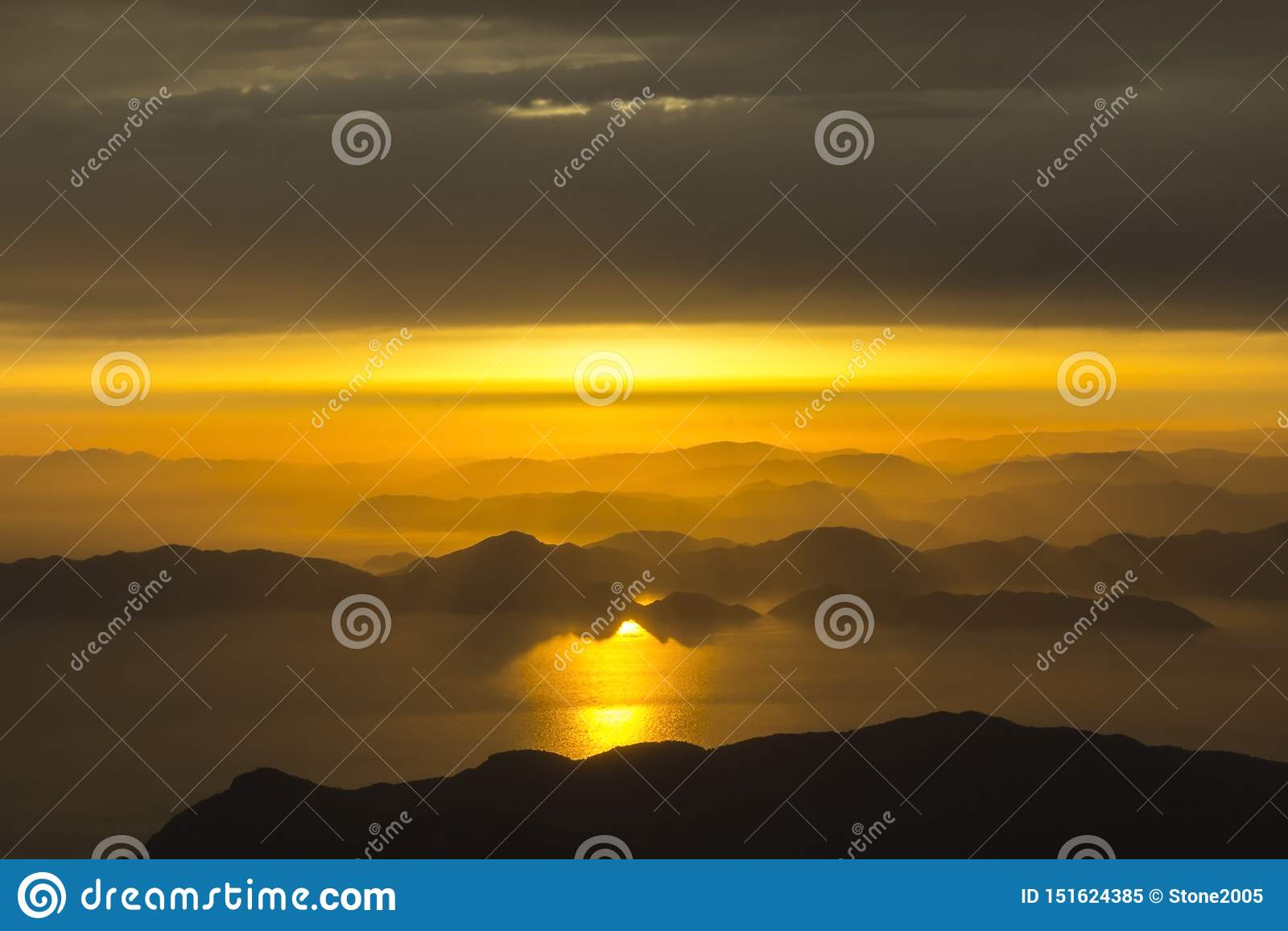 Góry i morze, zmierzch, niebo w pastelowych kolorach, lekka mgiełka, plama