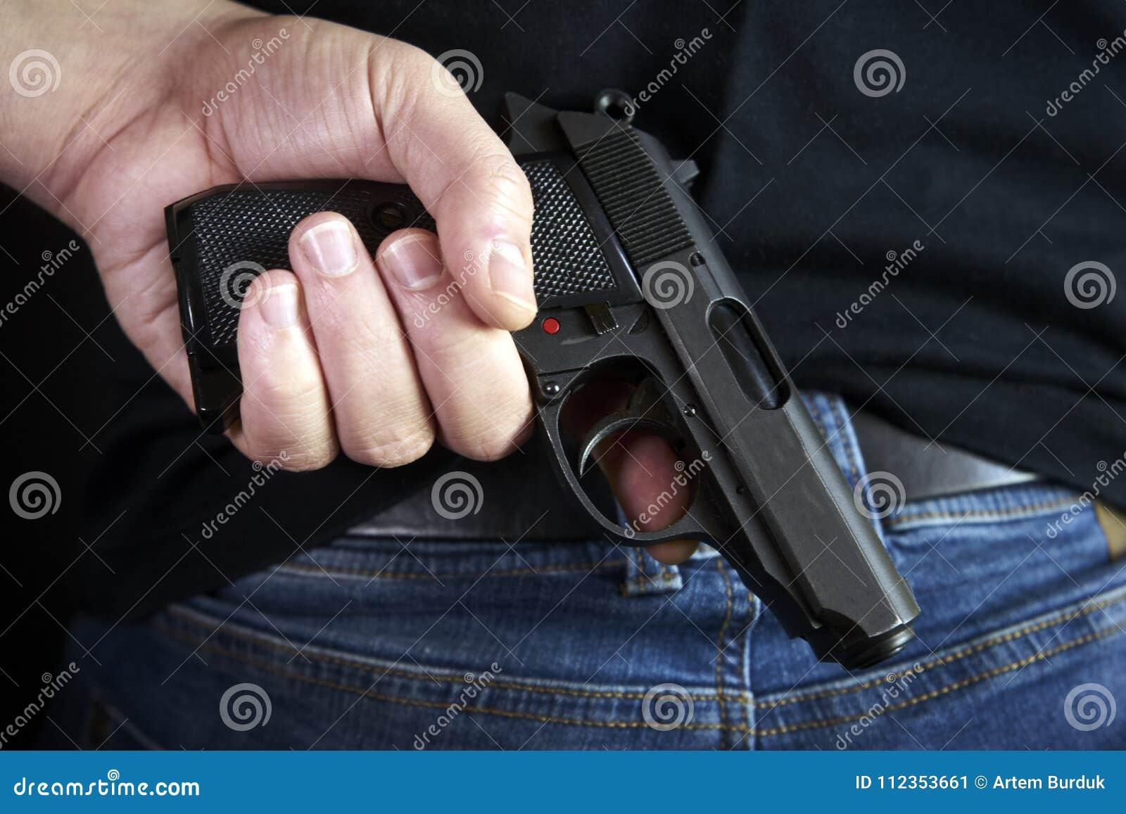 Gömt vapen i för händer sida tillbaka till mannen i jeans