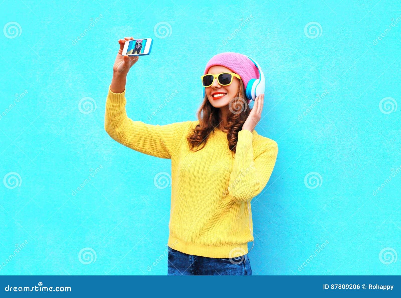 Gör den kalla flickan för mode i lyssnande musik för hörlurar som tar fotoet, självståenden på att bära för smartphone färgrik kl