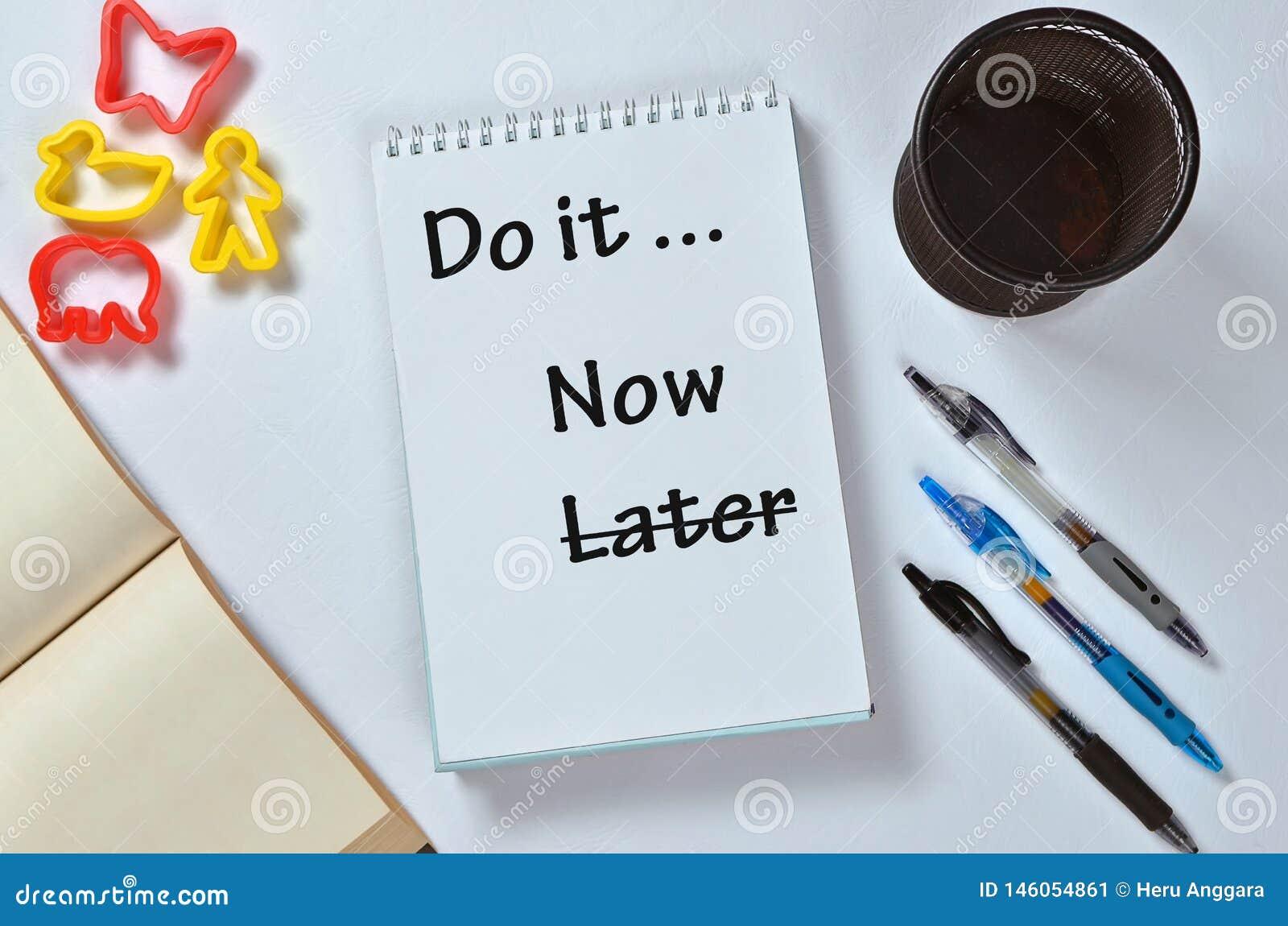 Gör det nu inte senare text på notepaden med kontorstillbehör Aff?rsmotivation, inspirationbegrepp