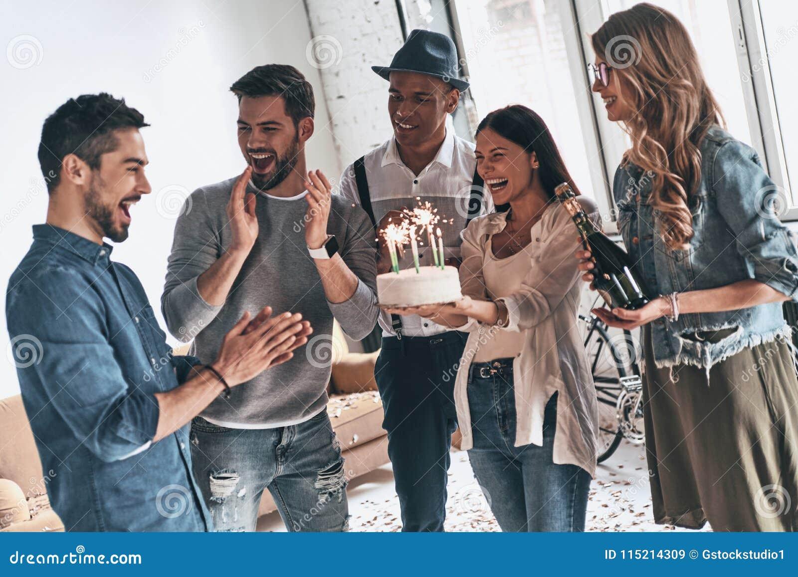 Gör en önska! Lycklig ung man som firar födelsedag bland vänner