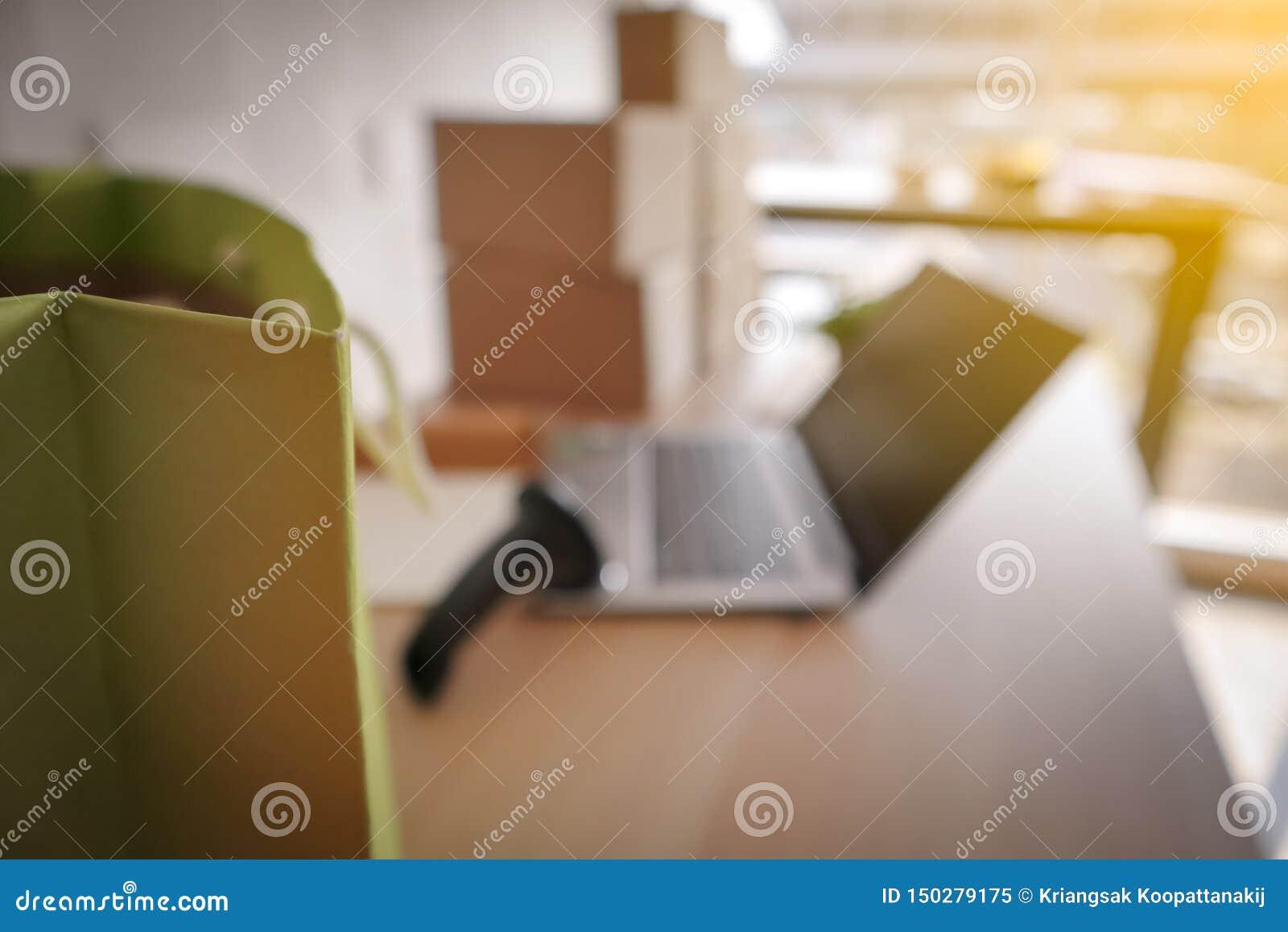 Gör suddig bilden av den gröna shoppa pappers- påsen med bärbara datorn