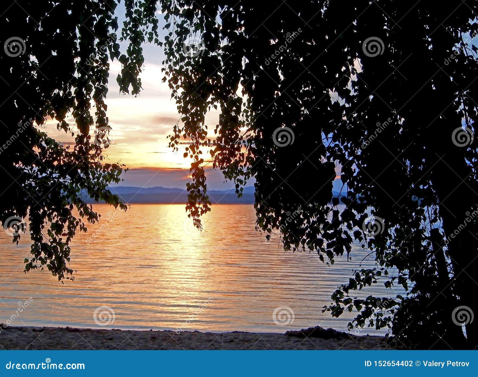 Göra mörkare av solnedgånghimlen över sjön med färgrika moln och mörka konturer av träd, guld- timme