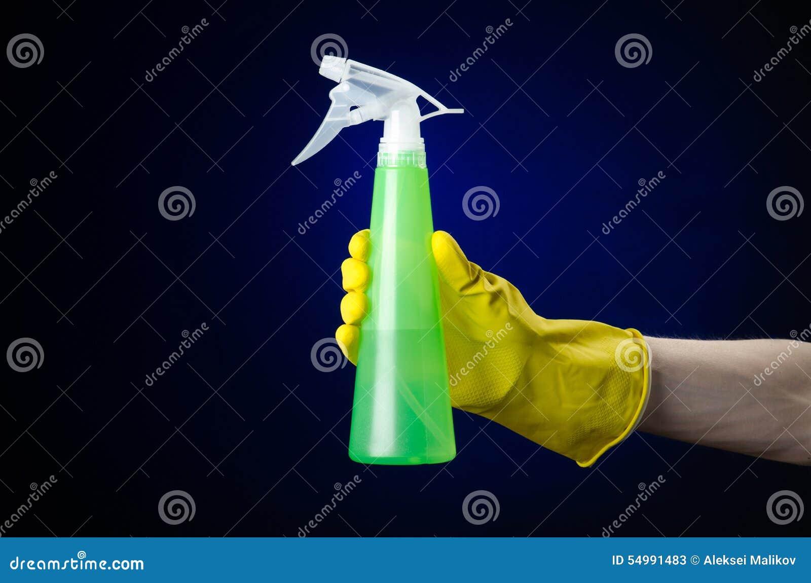 Göra ren hus- och rengöringsmedeltemat: mans hand i en gul handske som rymmer en grön sprejflaska för att göra ren på ett mörker