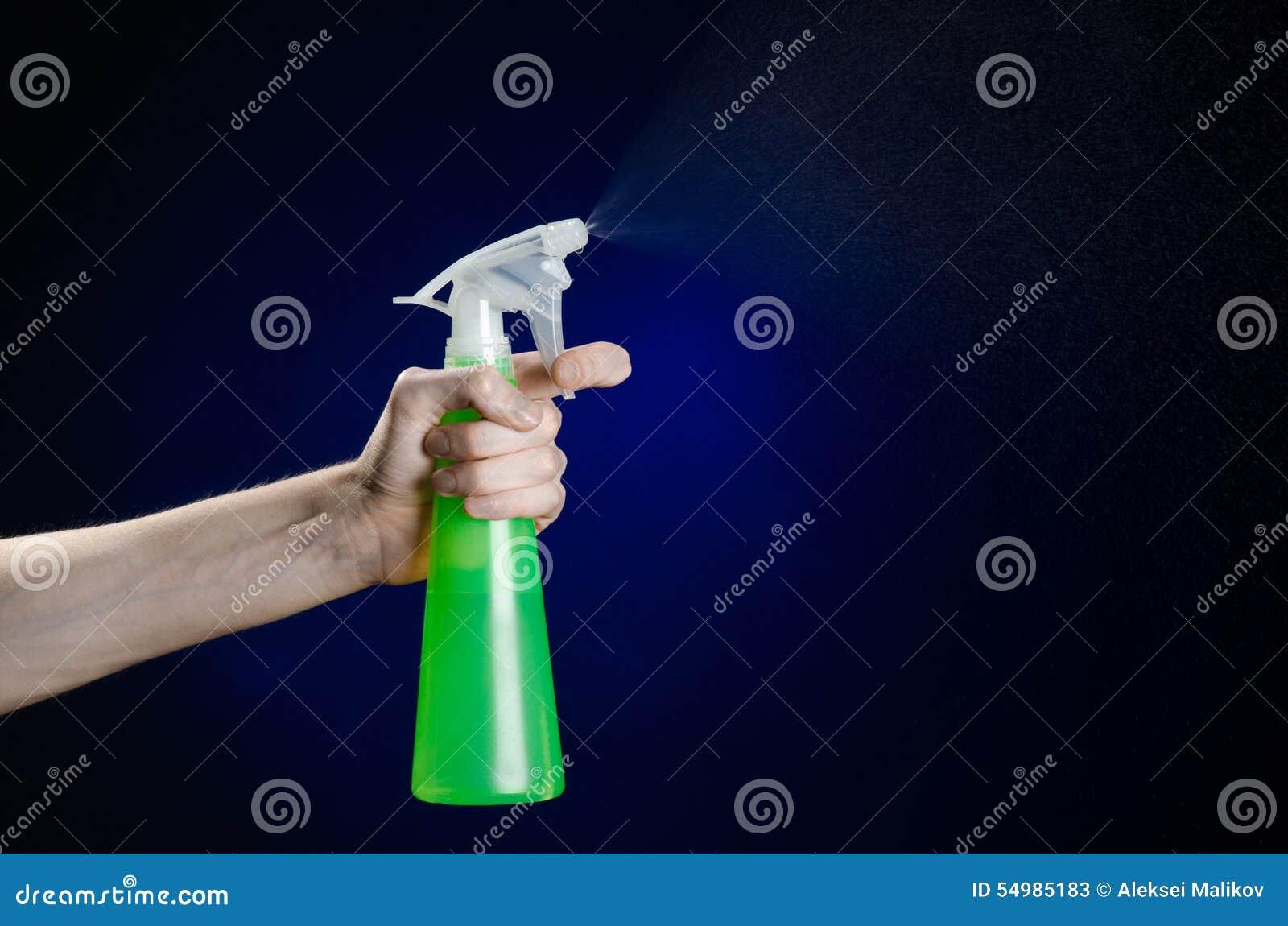Göra ren hus- och rengöringsmedeltemat: mans hand som rymmer en grön sprejflaska för att göra ren på ett mörker - blå bakgrund